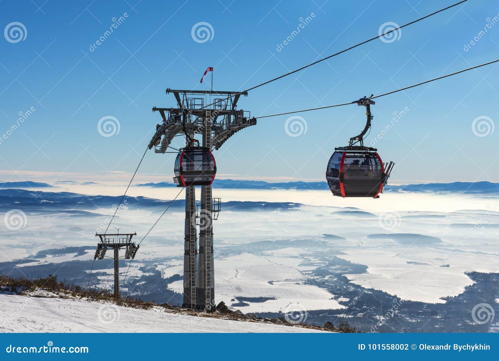 GONDELBAHN Kabine des Skiliftes im Skiort am frühen Morgen an der Dämmerung mit Bergspitze im Abstand