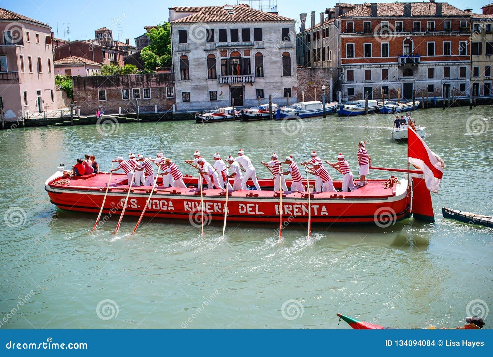 Gondeliers состязаясь в Regata Storica, Венеции, Италии