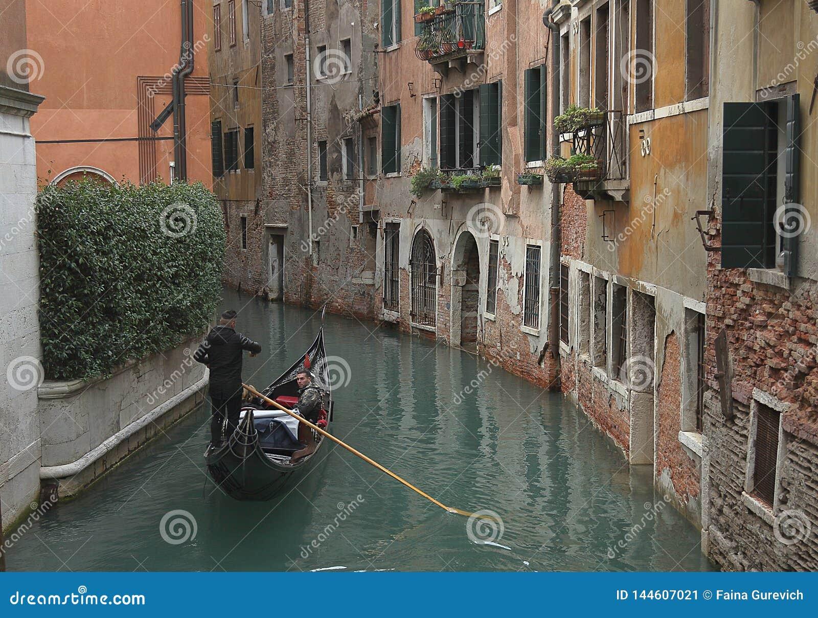 Gondol med turister på en smal kanal som omges av gamla byggnader i Venedig