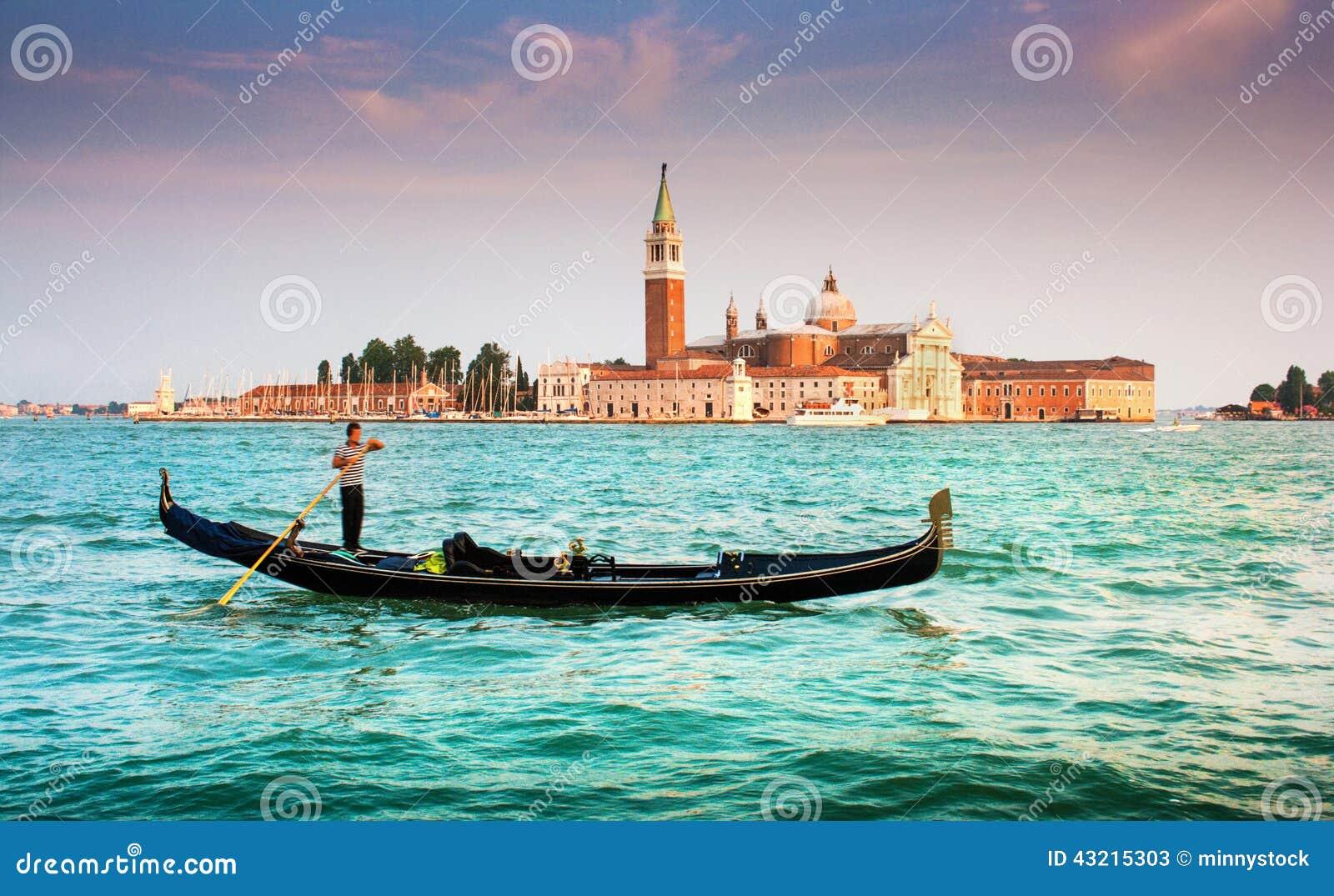 Gondol på kanalen som är stor med San Giorgio Maggiore på solnedgången, Venedig, Italien