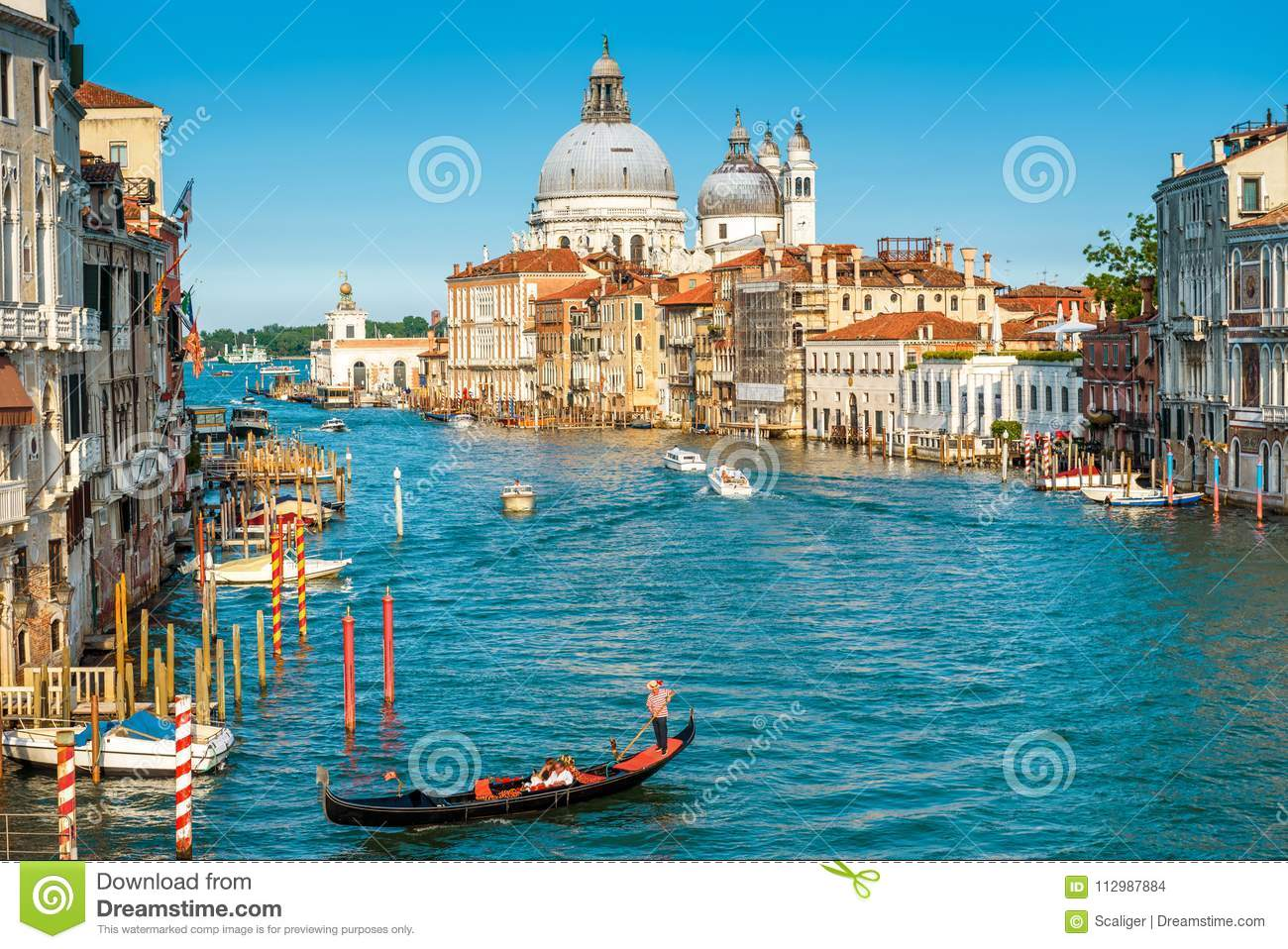 Gondola with tourists sails along the Grand Canal in Venice, Italy