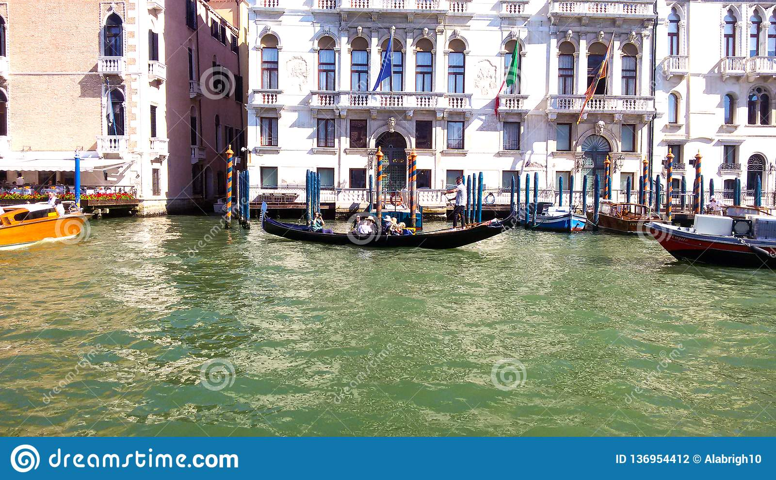 A gondola transports its passengers through a canal in Venice.