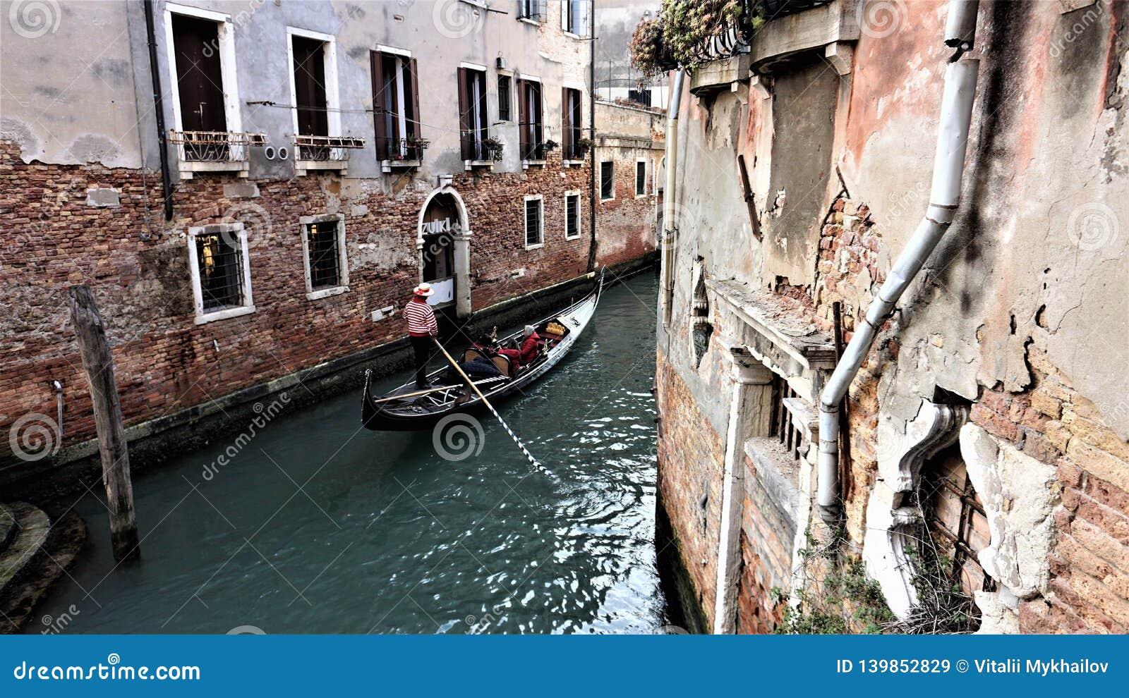 Gondoleiro Venetian que flutua em uma gôndola através das águas do canal entre as casas de Veneza Itália