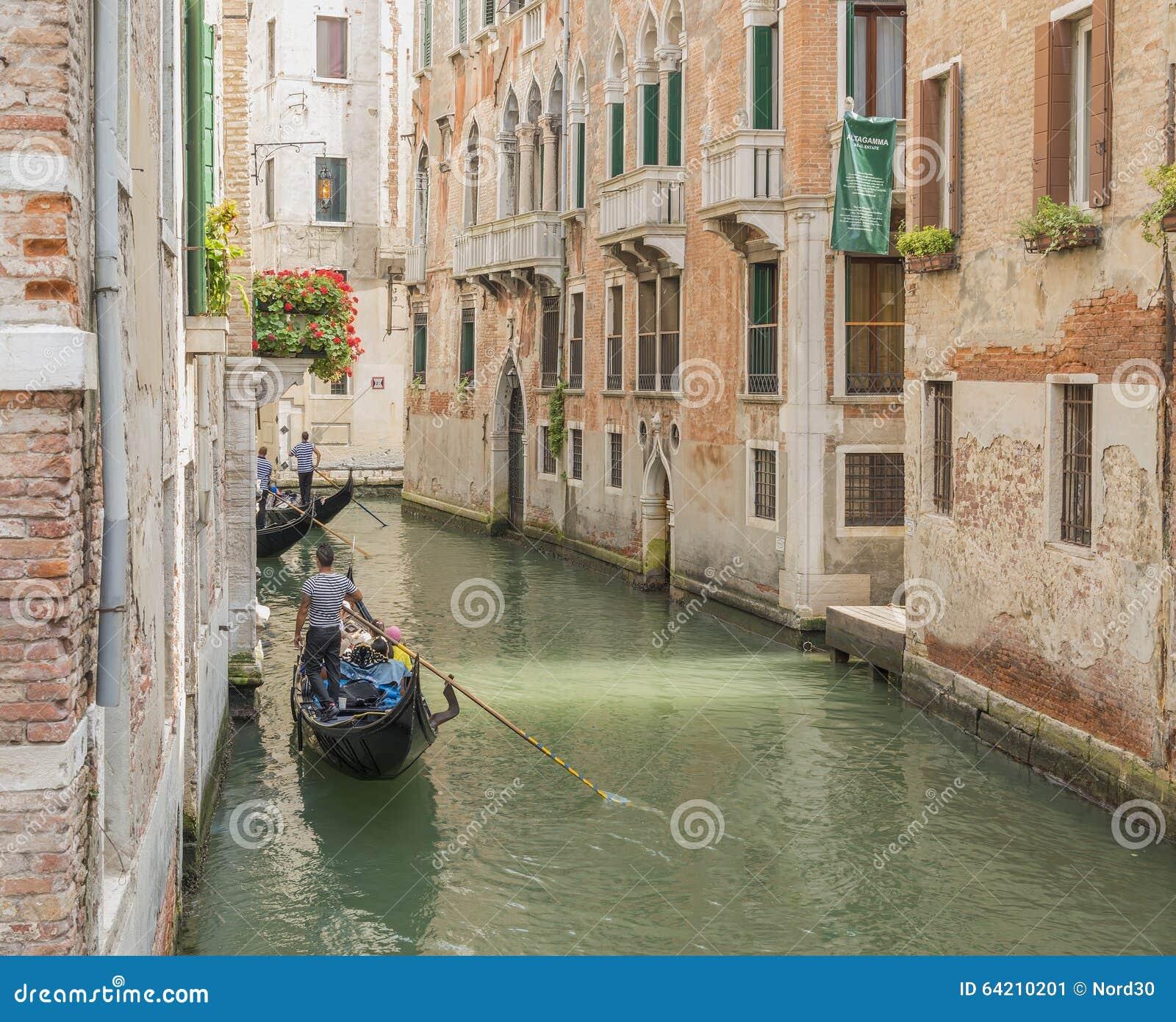 Gondolero veneciano que lleva en batea la góndola con verde