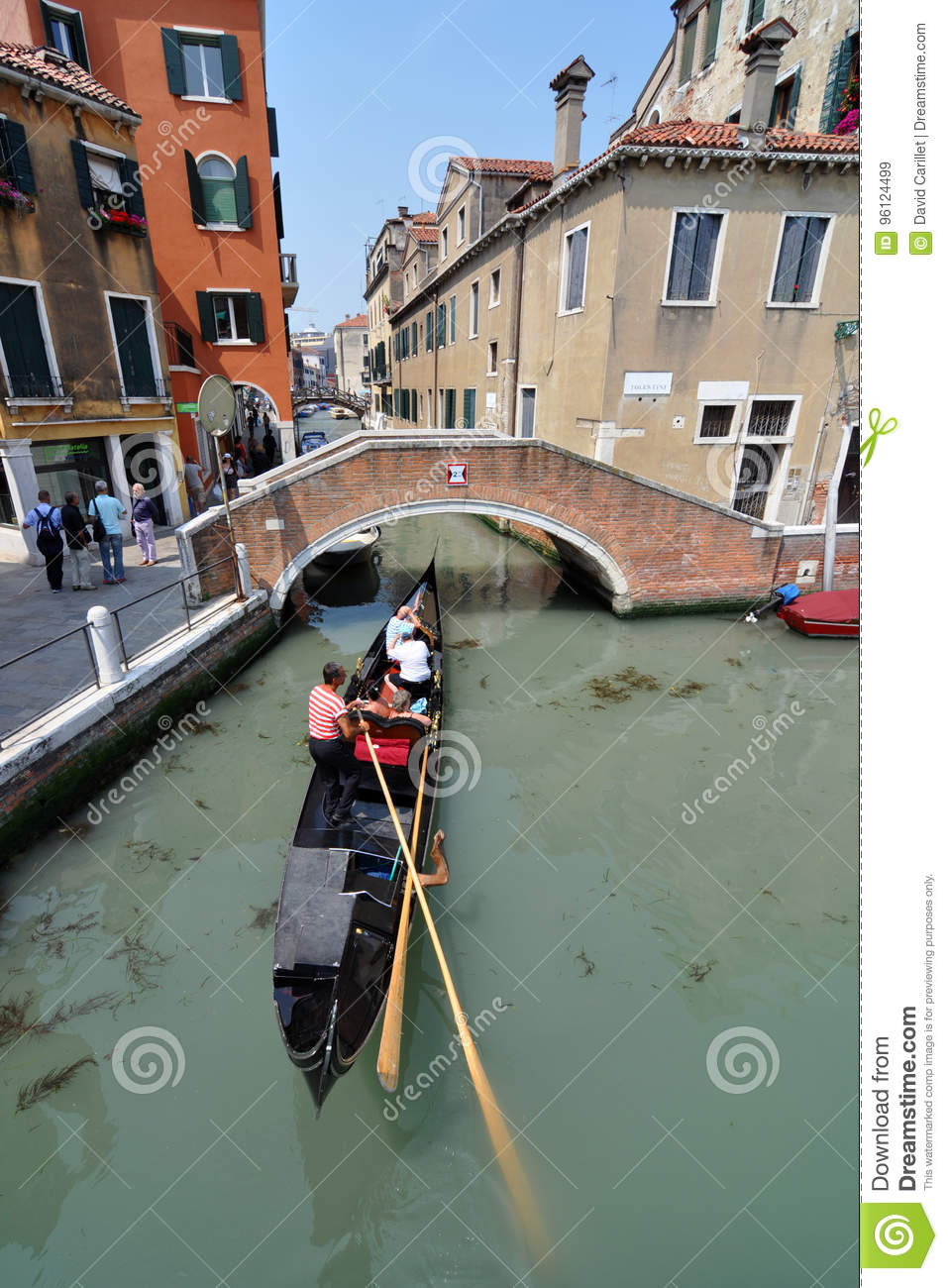 A gondolier in Venice navigates his gondola through one of the city`s many canals