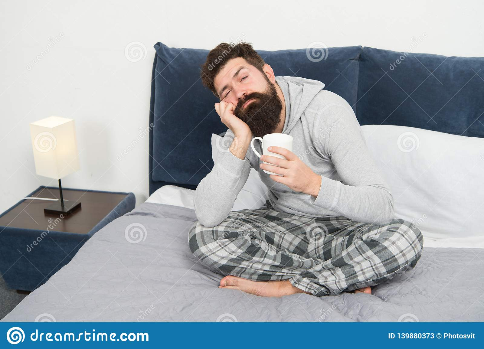 Good gay begins from cup of coffee. Coffee affects body. Man handsome hipster relaxing on bed with coffee cup. Coffee
