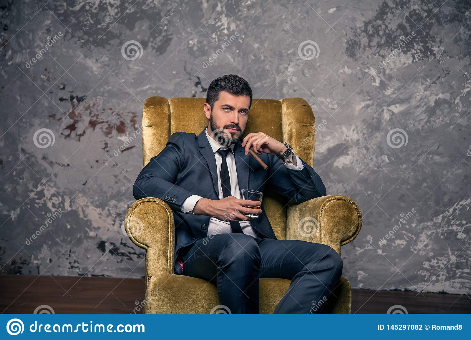Good looking handsome businessman is taking a rest sitting on the chair and drinking whisky with a cigar and thinking. wearing