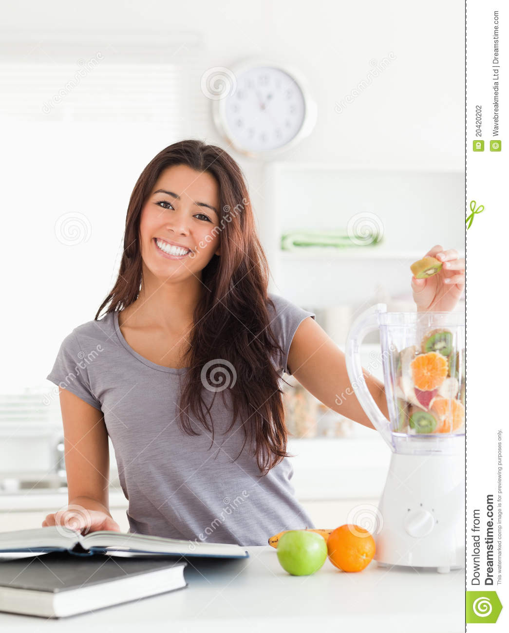 Good looking woman consulting a notebook while filling a blender with ...