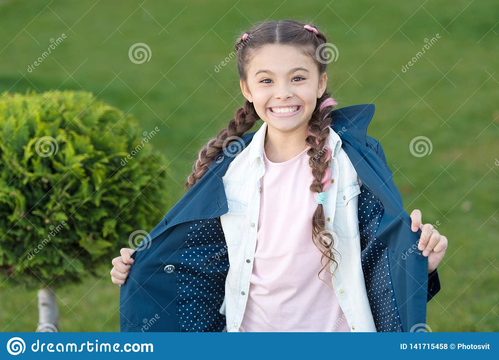 Good mood. Autumn weather. Cypress tree. Happy child with thuja. Positive kid. Little girl with trendy hairstyle. Spring