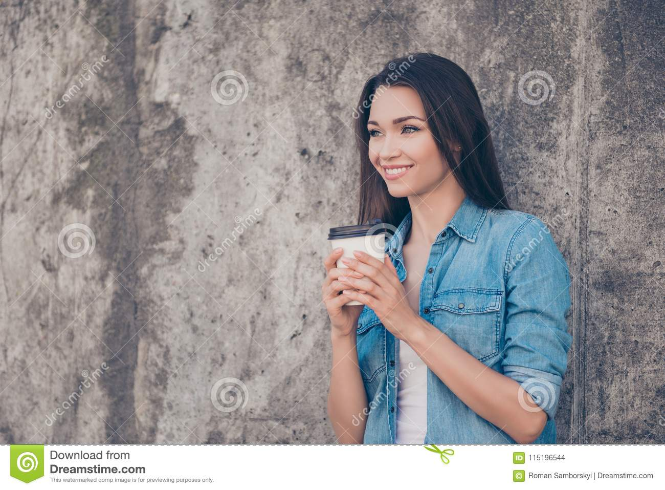 Good morning! Cheerful pretty young serene brunette lady is having hot tea near concrete wall outside, smiling, wearing cozy casua