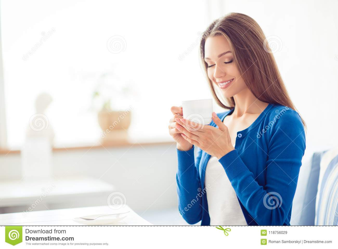 Good morning! Close up portrait of charming dreamy brunette young girl drinking coffee. She is sleepy and relaxed, in casual blue