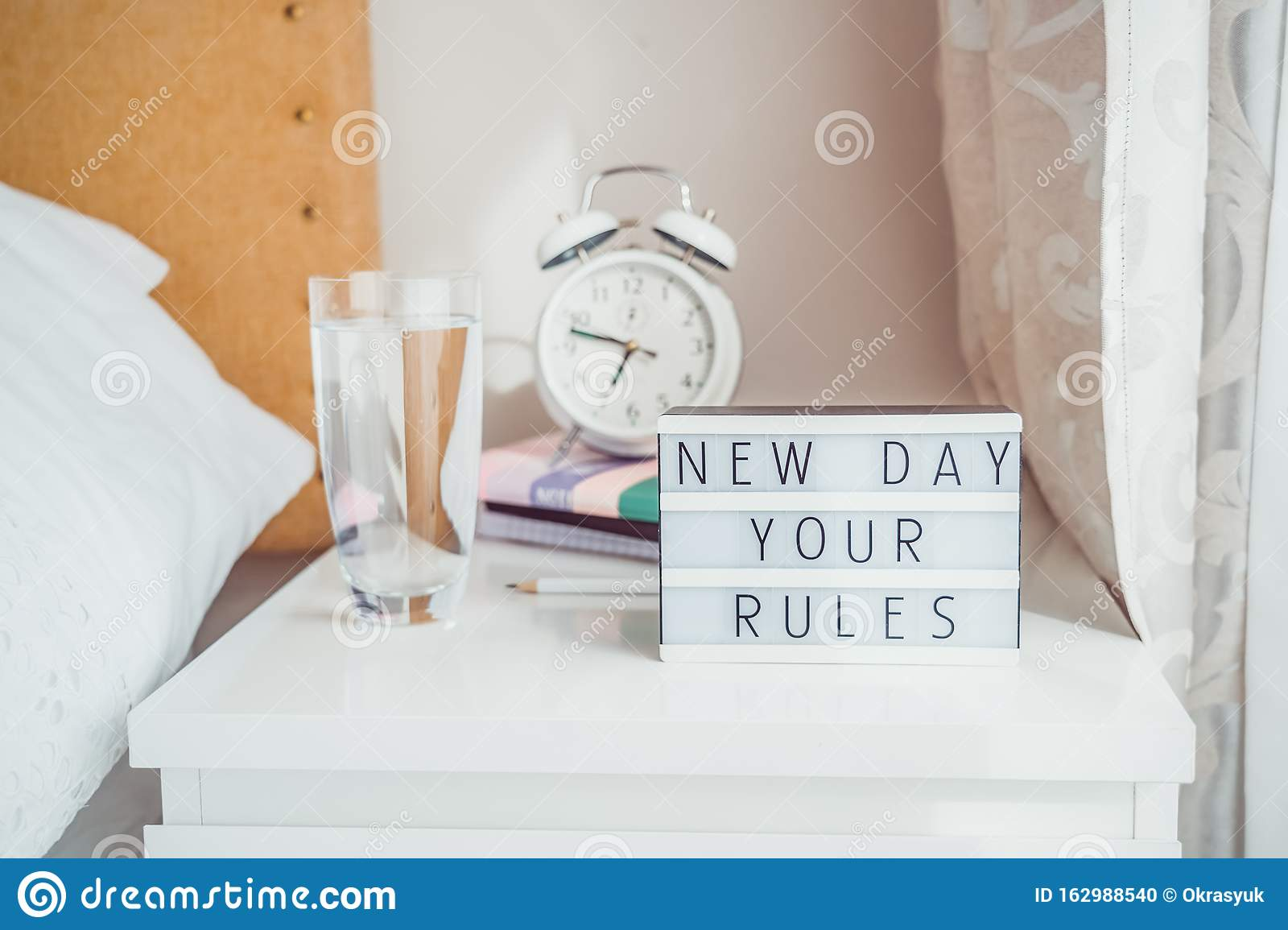 Good morning concept. Inspiration Motivational Life Quotes New day your rules message on lightened box with alarm clock, notebooks