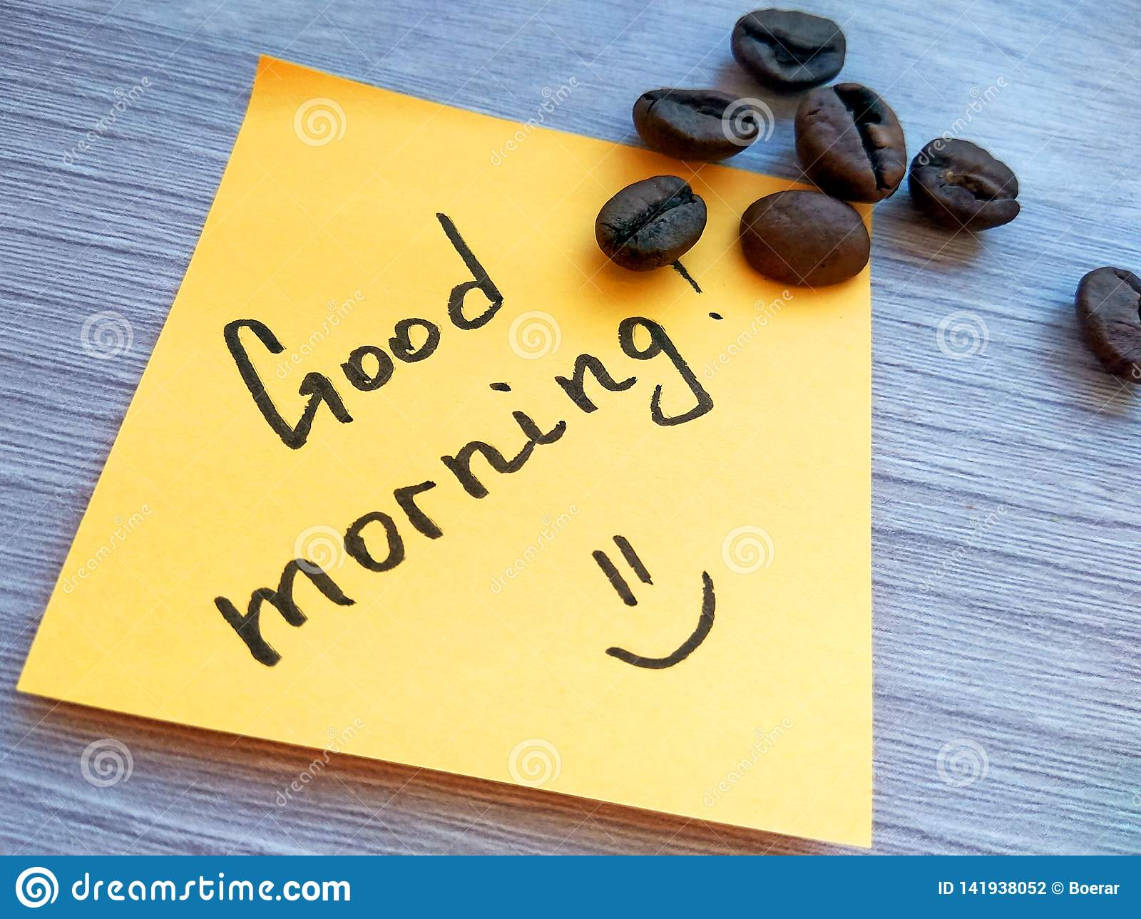 Good morning handwritten message on orange sticky note with coffee beans on wooden background