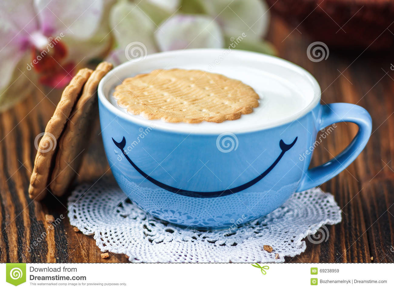 Good morning or Have a nice day message concept - bright blue cup of milk with cookies. Cup of milk with smile. Health and diet co