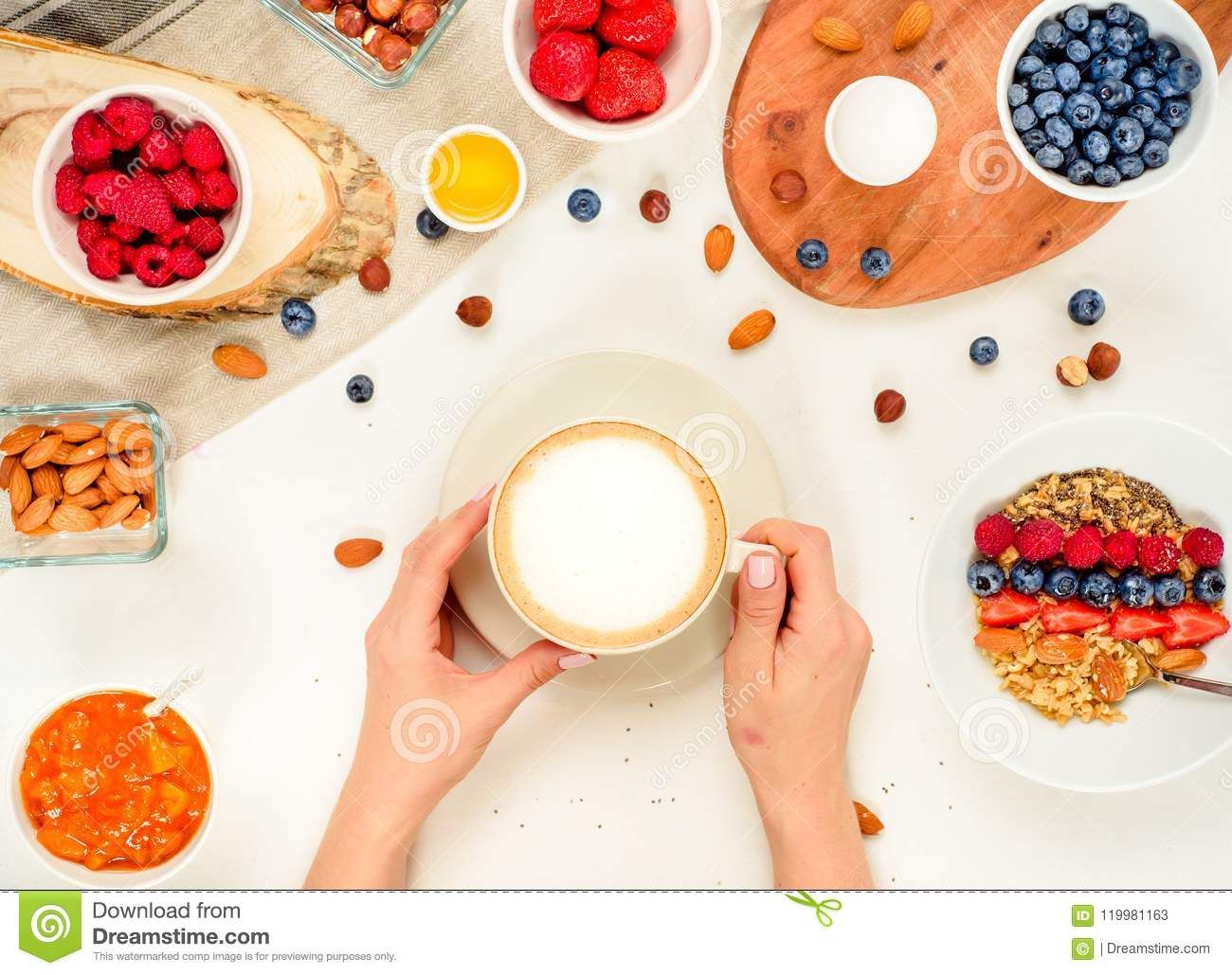 Good morning - healthy breakfast background with oatmeal coffee, berries, egg, nuts. Coffee, hands, hold, cup. White wooden food b