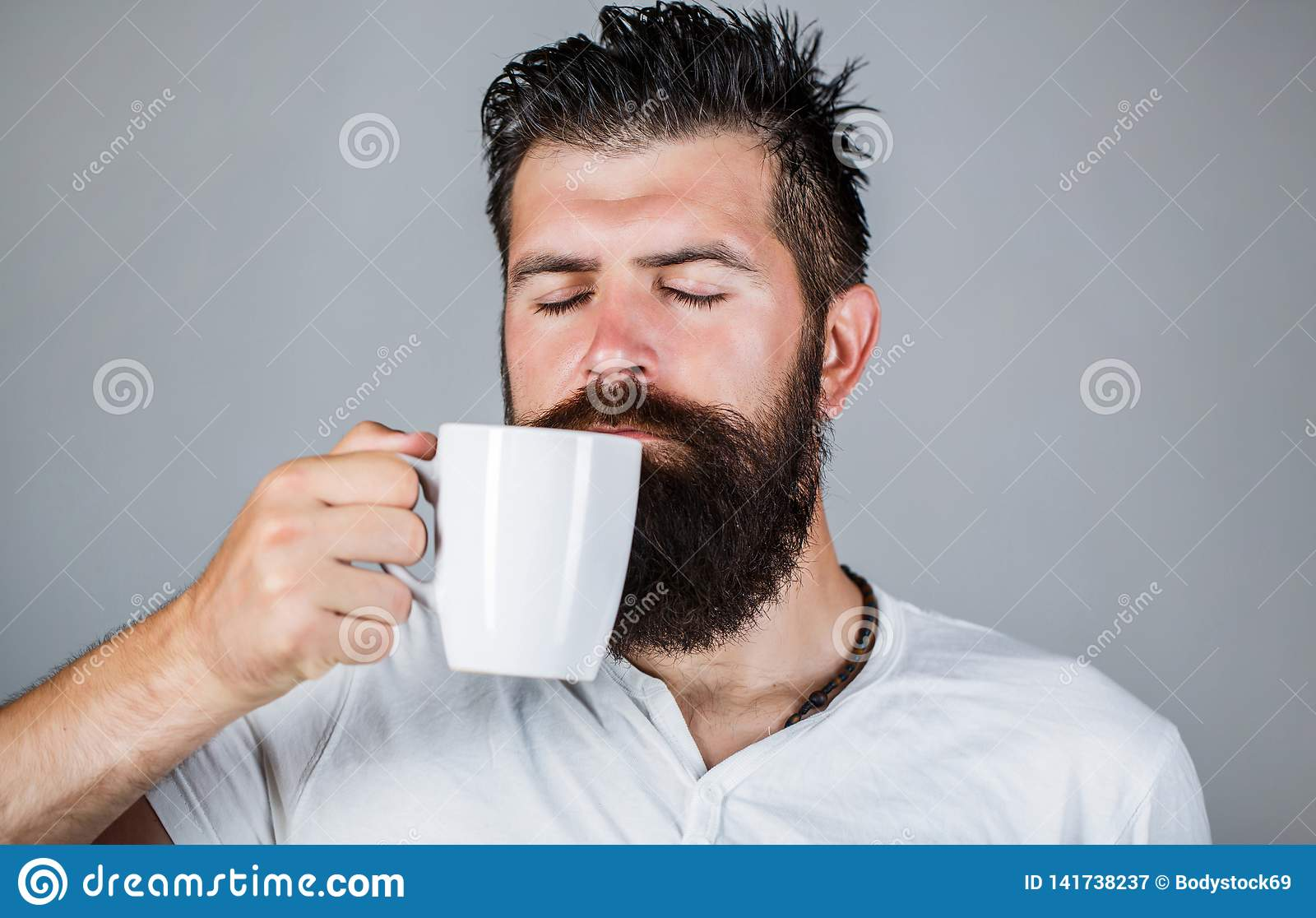 Good morning, man holding a cup tea. Morning concept. Handsome bearded male holds cup of coffee, tea. Smiling hipster