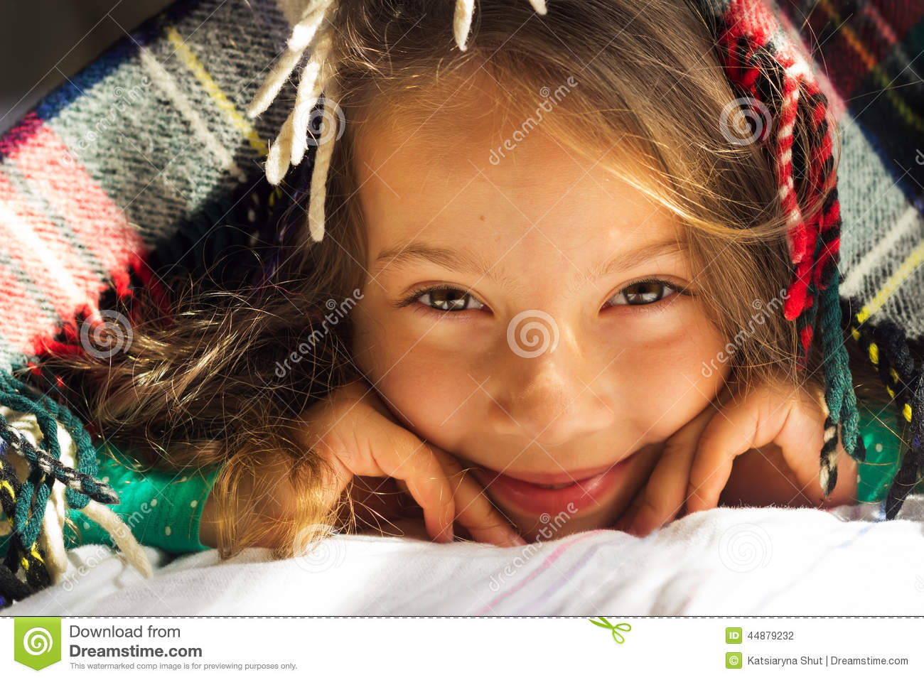 Good morning portrait of cute curly smiling school girl look out from warm plaid