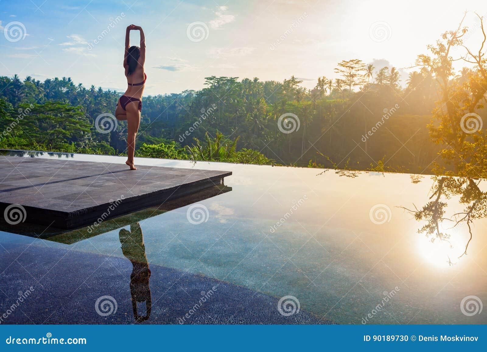 Good morning with woman yoga meditating on sunrise background.