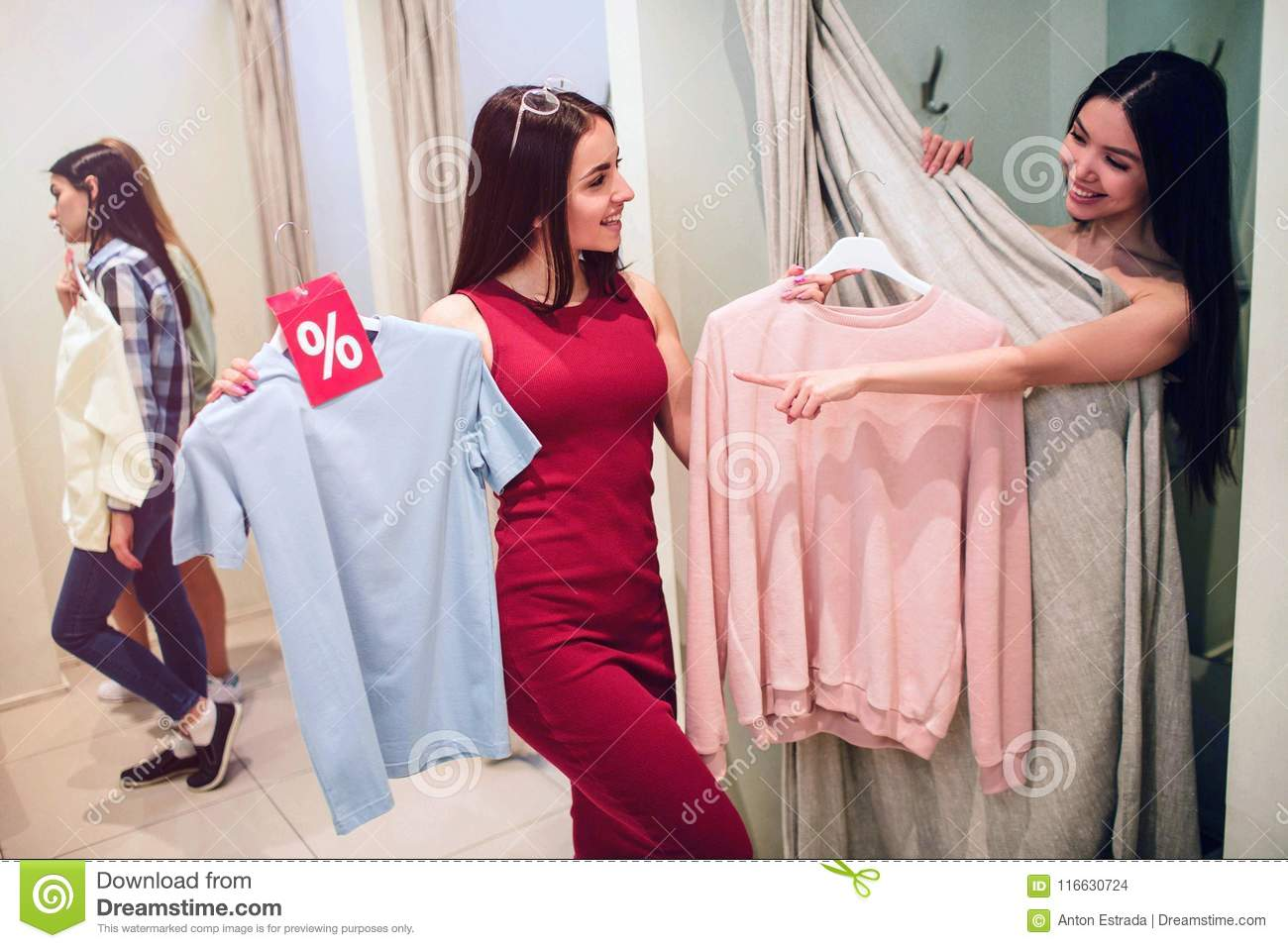 Good picture of asian girl trying on herself different clothes. Girl in dress gives her pink shirt but asian girl wants