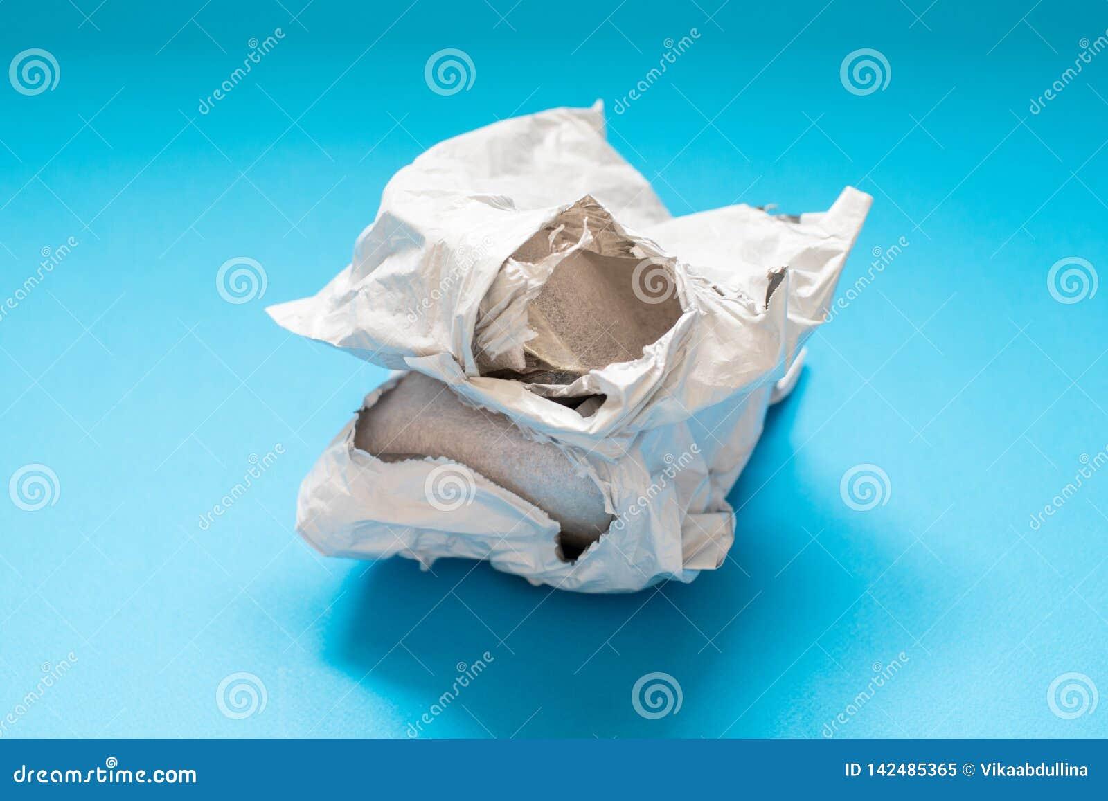 Damaged polyethylene envelope on blue background. Plastic Postal Mailing Bags