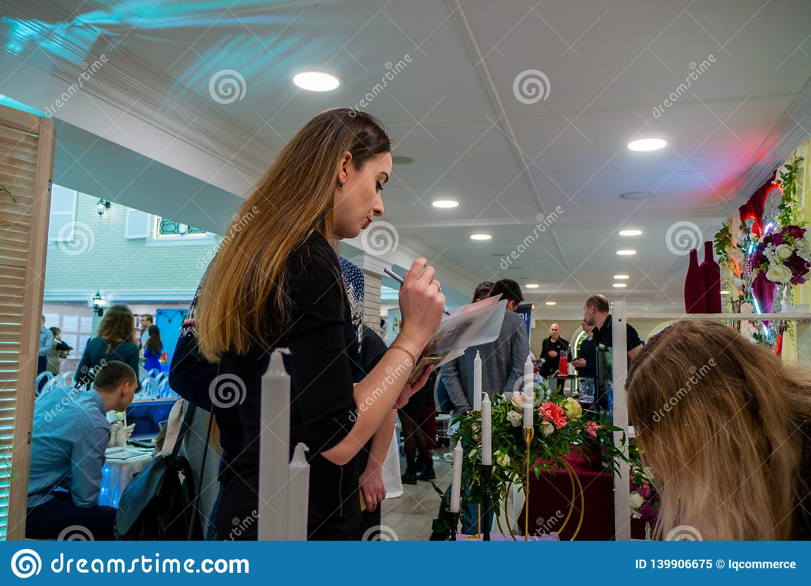 A Lady Checking A List At A Wedding Exhibition Editorial