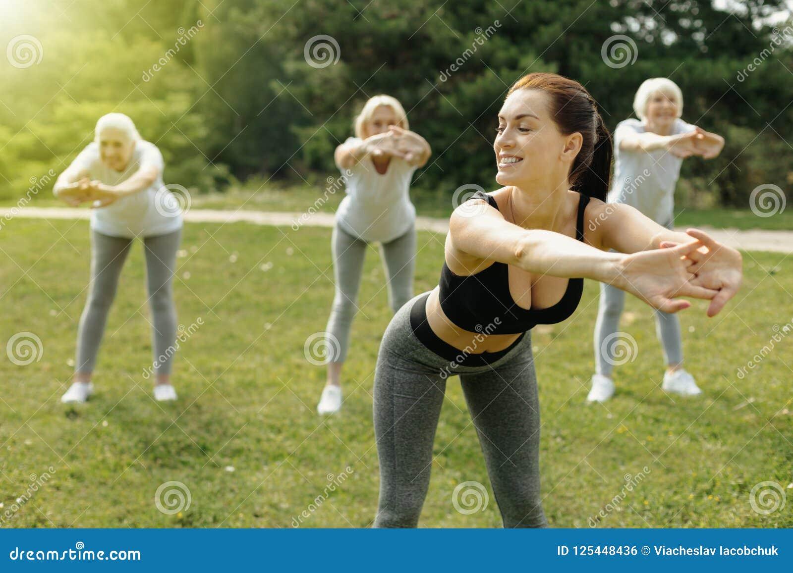 Positive minded woman training group of senior ladies