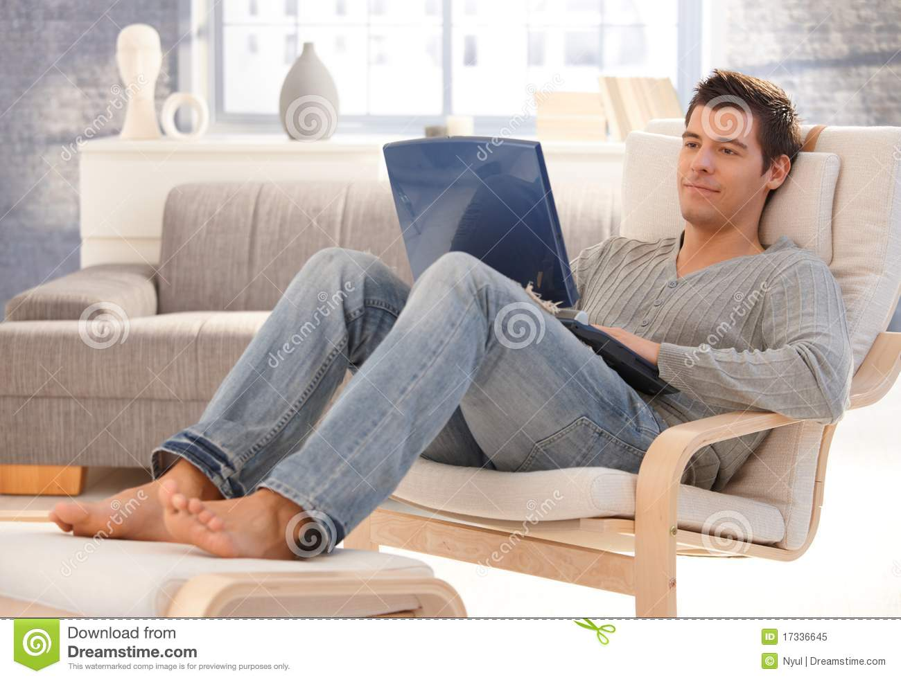 Goodlooking Young Man Relaxing At Home With Laptop Royalty