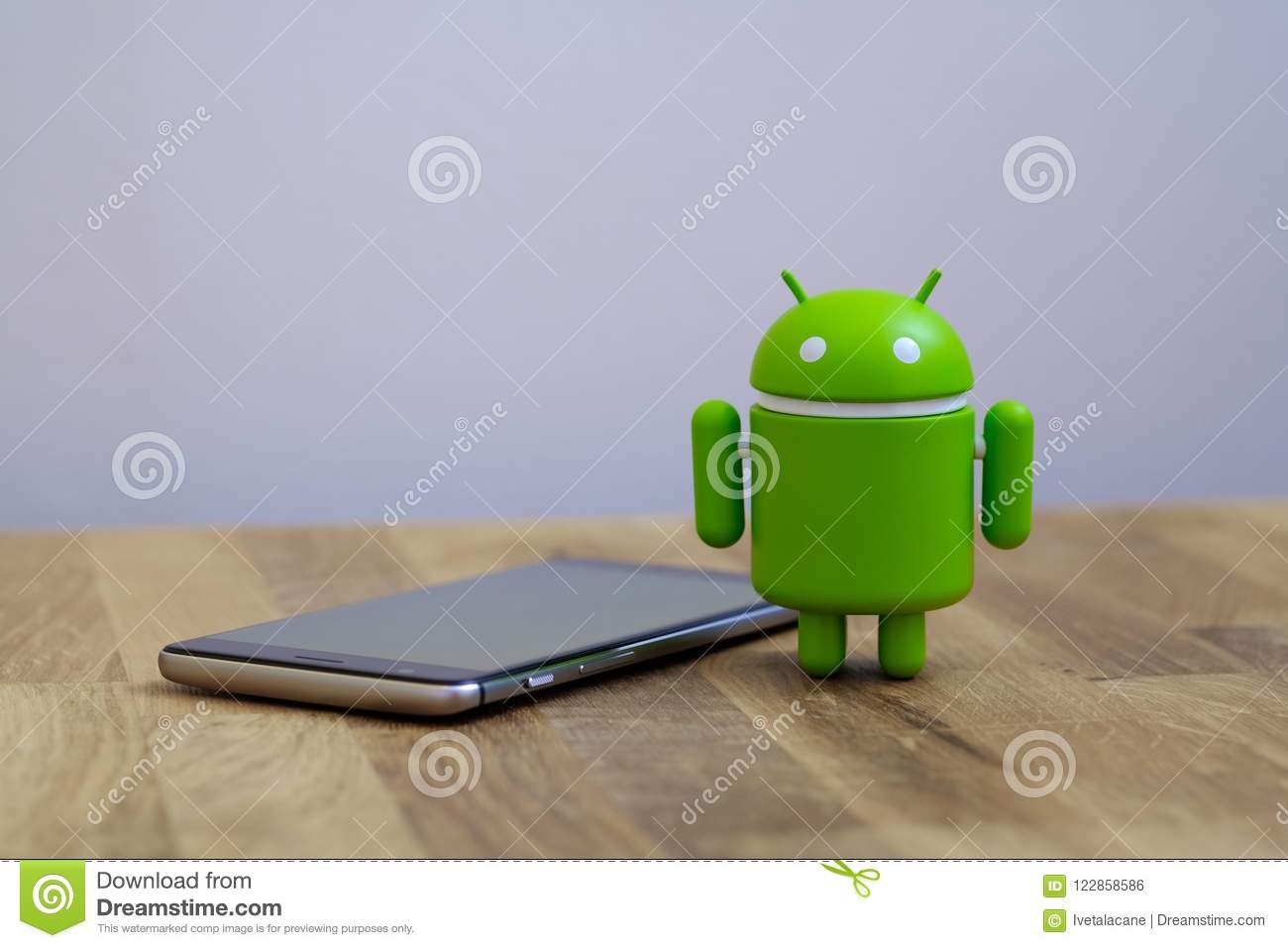 Google Android figure standing next to smart phone