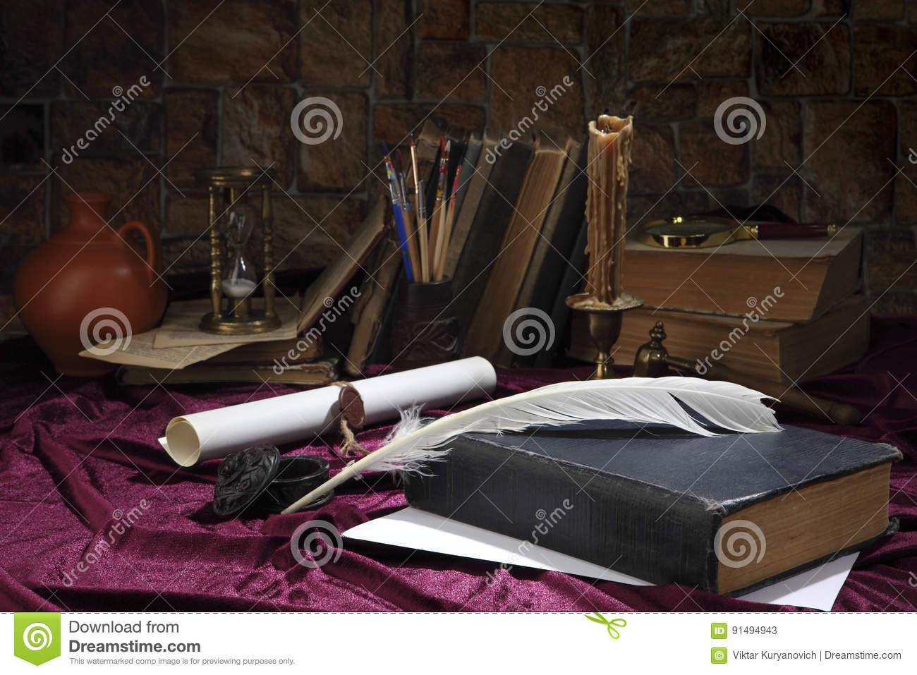 A goose feather, an inkwell, a scroll with a seal, a forged bronze candlestick with a candle, books, a magnifying glass and an hou