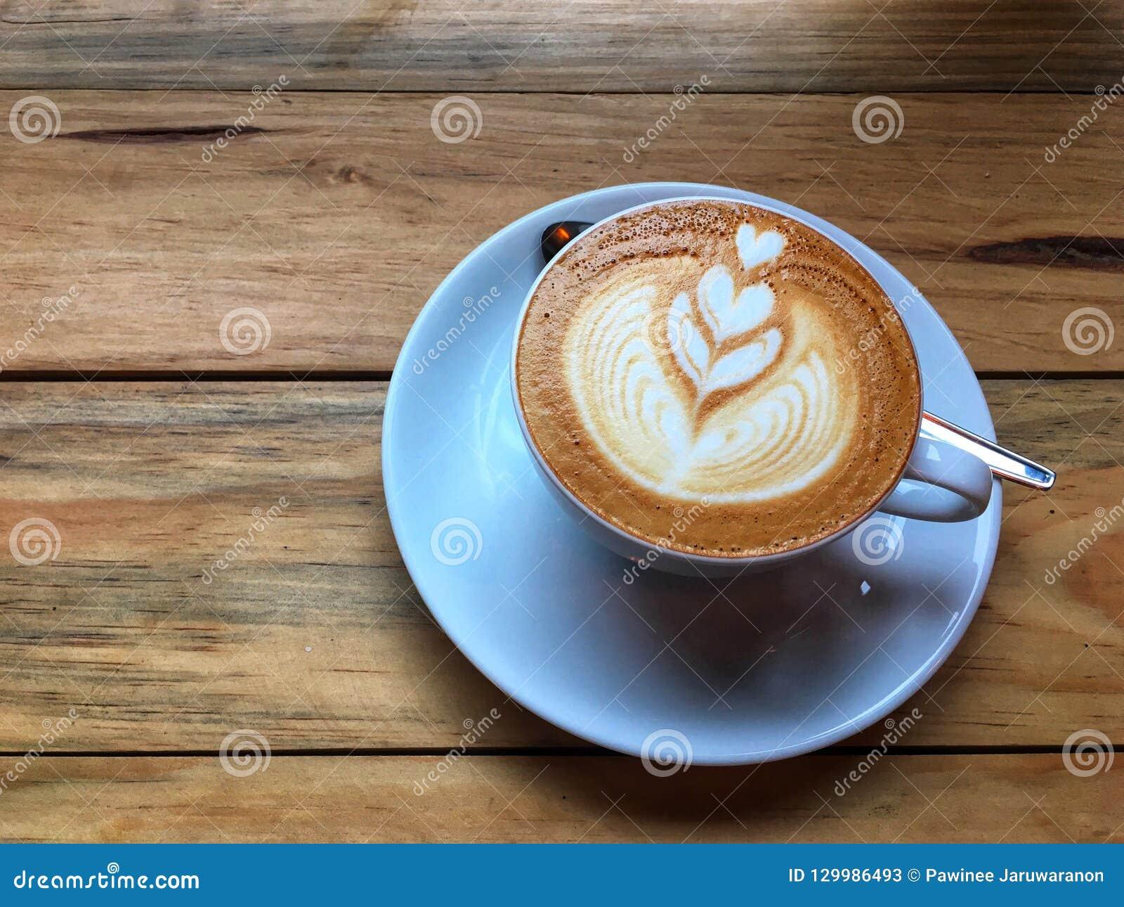 Gorąca cappuccino kawa w białym spodeczku z łyżką na drewnianym stołowym tle i filiżance Sztuka mleko piany rysunek