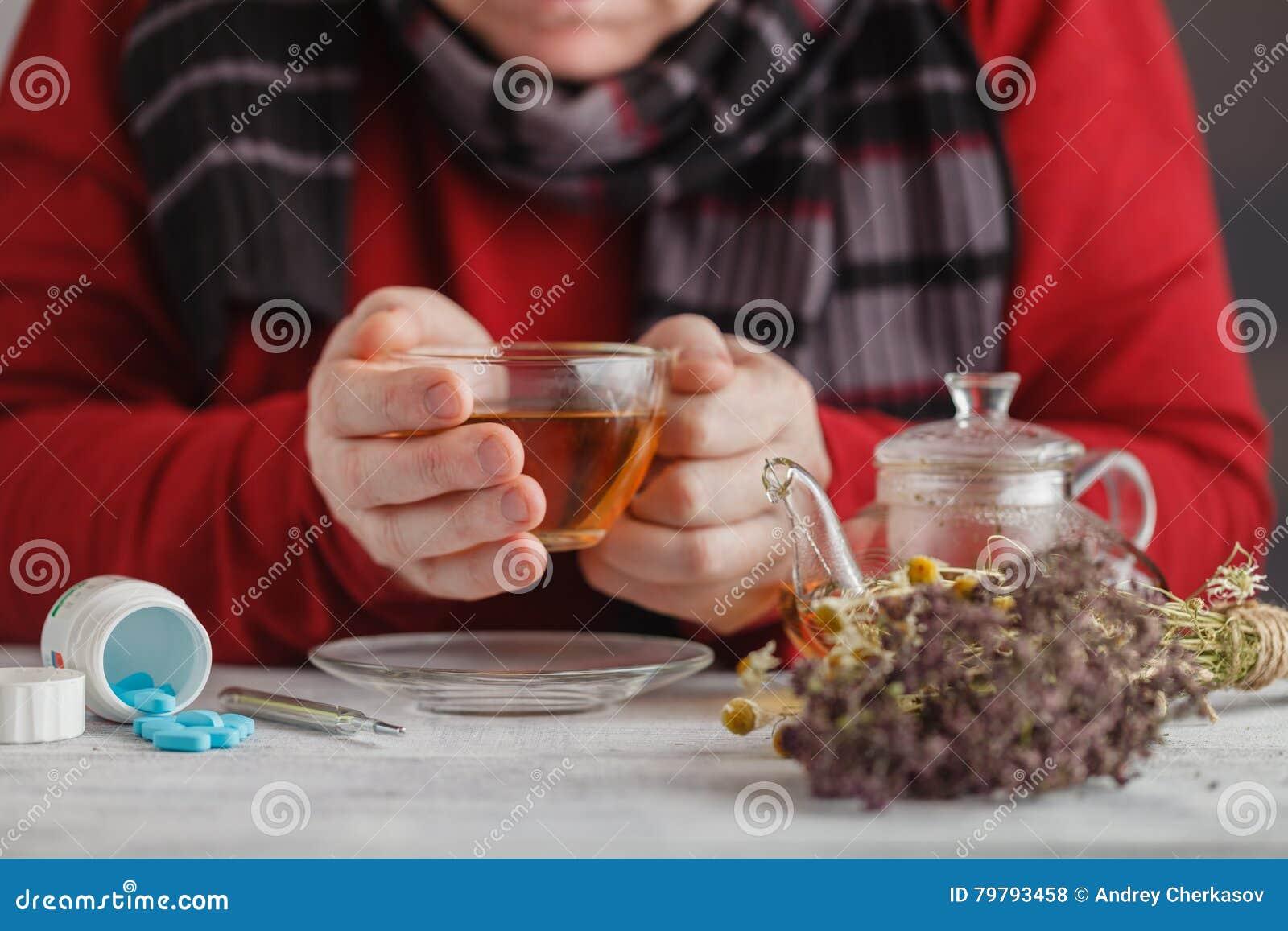 Gorąca herbata przeciw febrze Samiec patrzeje temperaturę na thermom