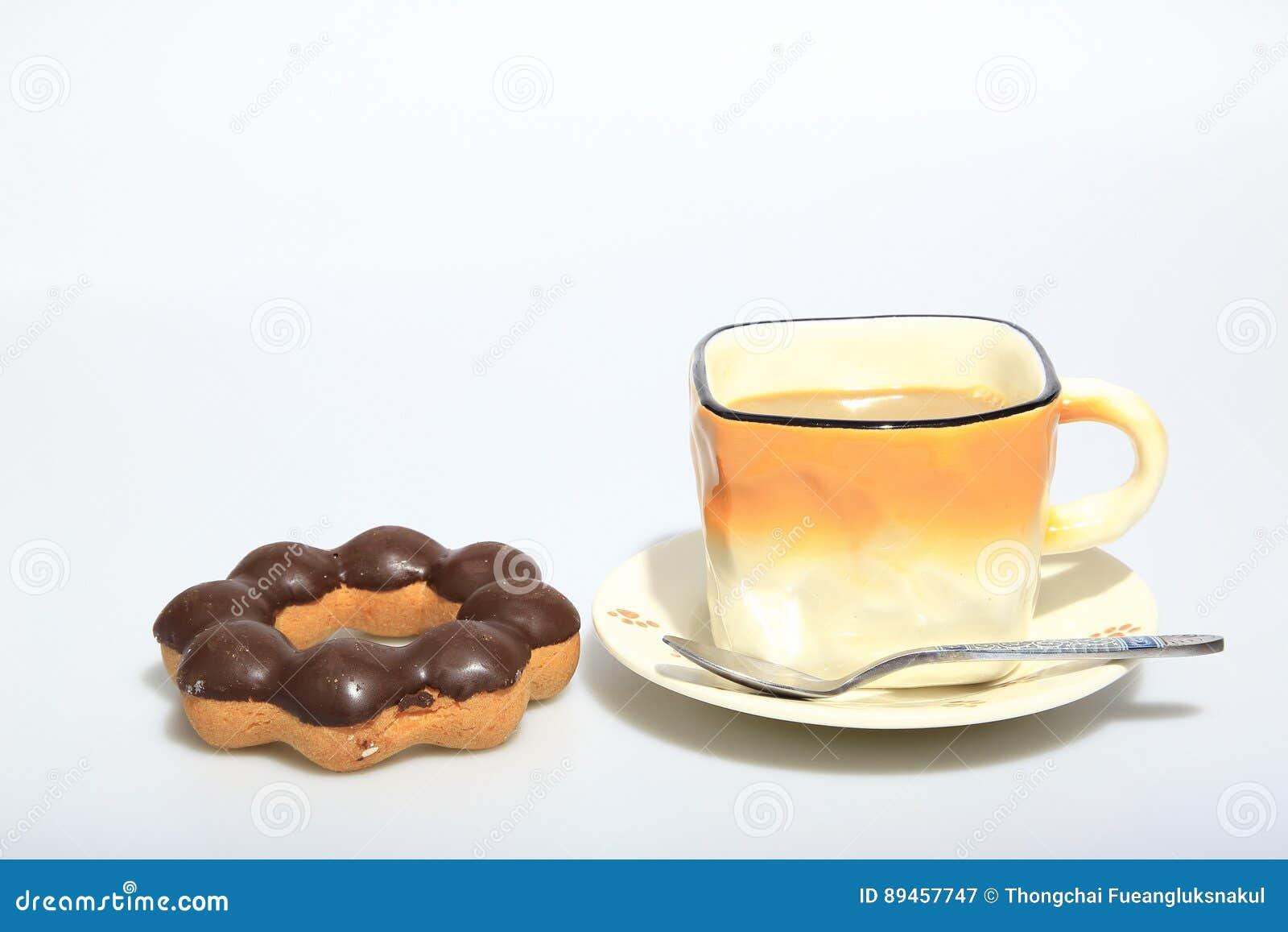 Gorąca kawa w filiżance z ciemnymi czekoladowymi donuts jako foods tło,