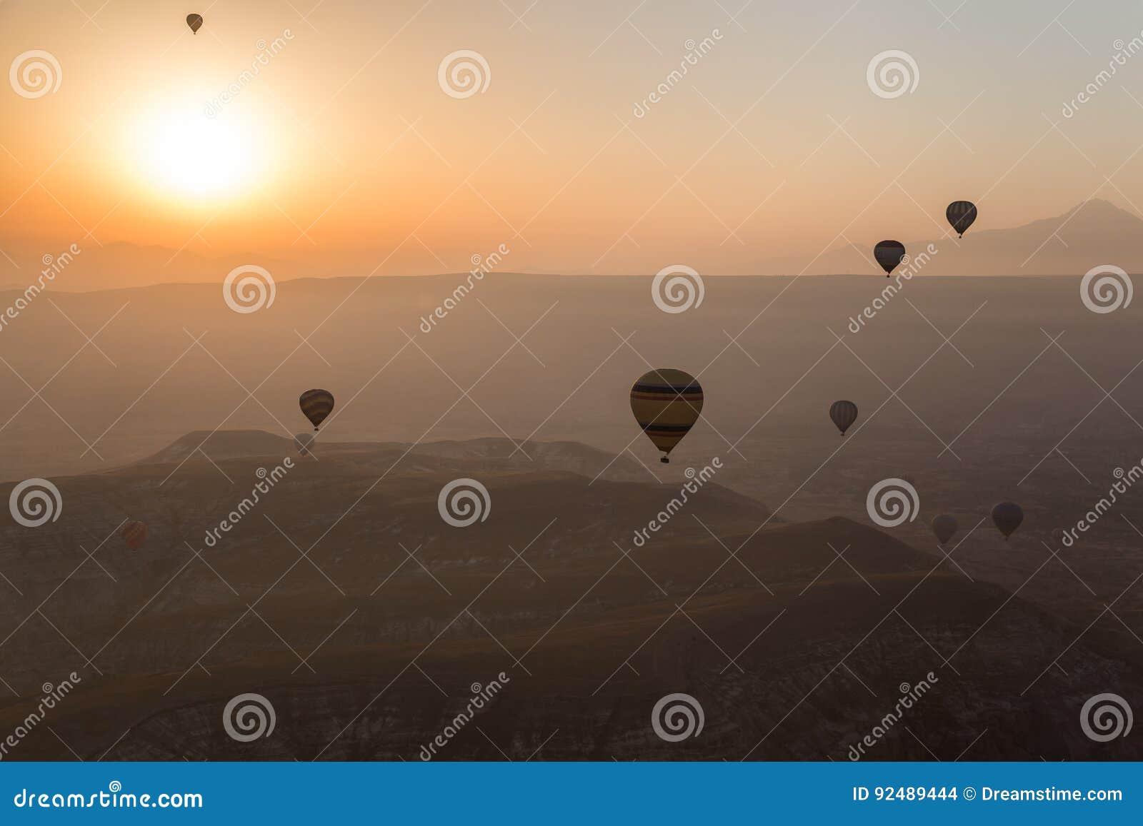 Gorące powietrze szybko się zwiększać wydźwignięcie nad Cappadocia horyzontem w wczesnym poranku