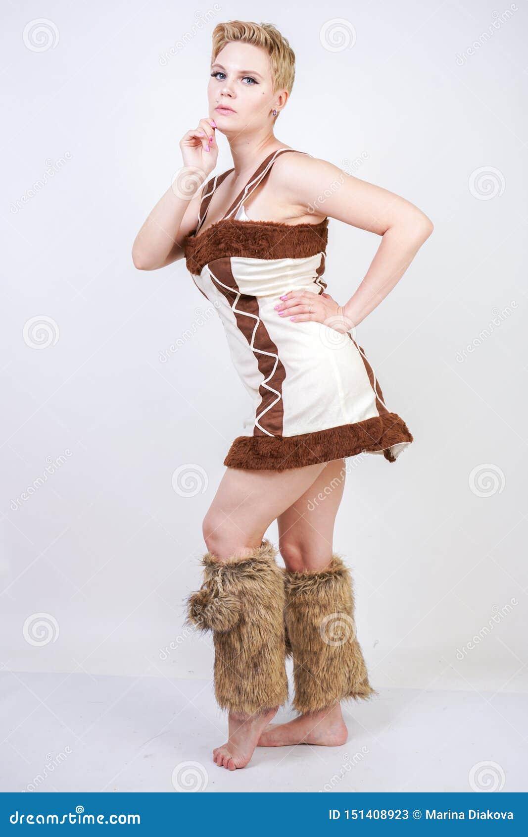 Gorący plus wielkościowa kobieta w futerkowym karnawałowym kostiumu pierwotny mężczyzna na białym tle w studiu piękna niewychowan