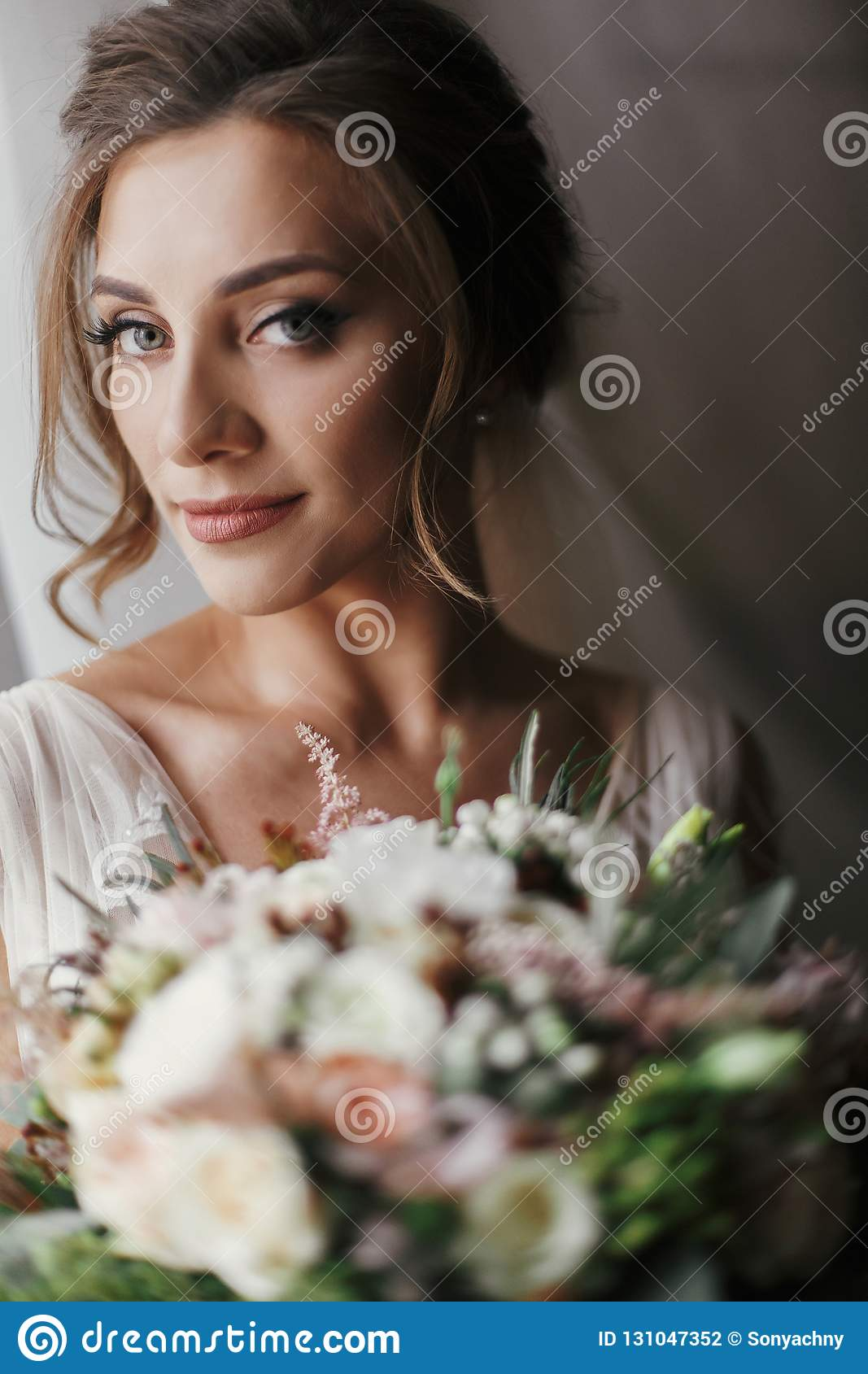 Gorgeous beautiful bride with bouquet posing at window in soft l