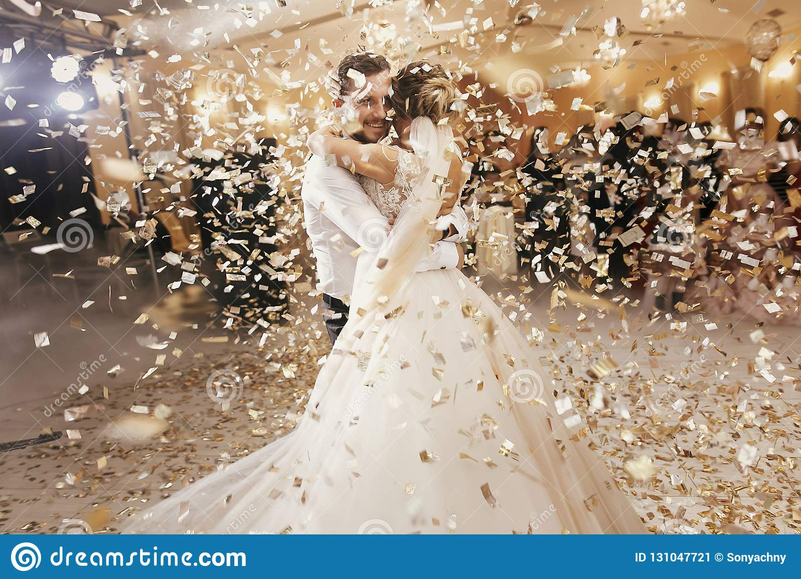 Gorgeous bride and stylish groom dancing under golden confetti a