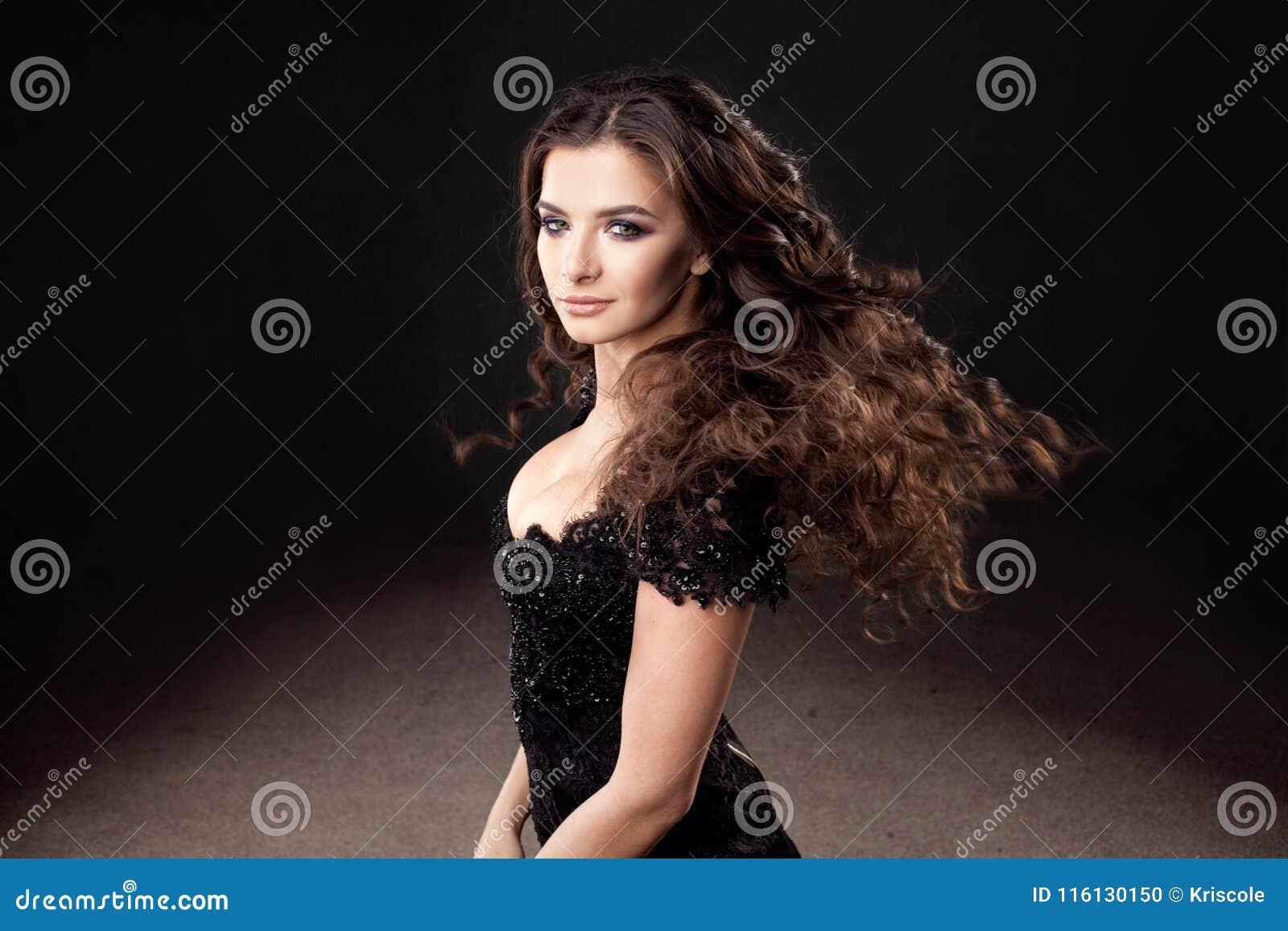 Gorgeous brunette girl in elegant black dress. Beautiful long curly hair.