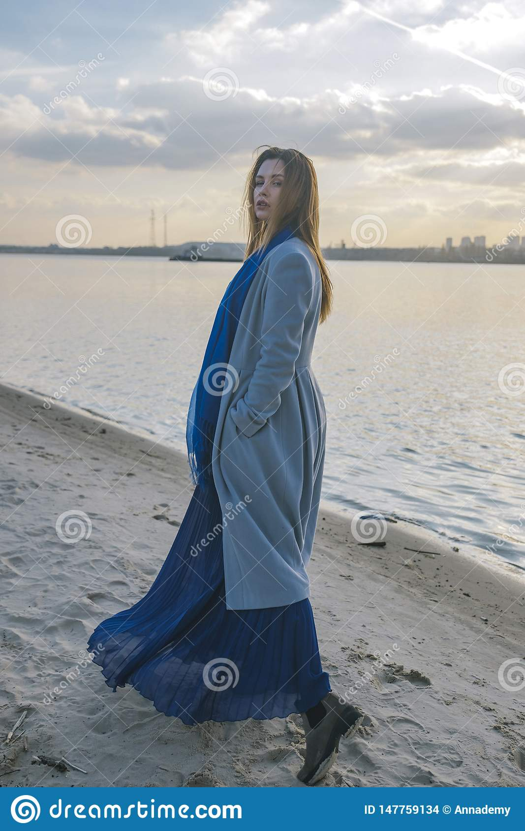Gorgeous european woman in warm coat and dress on a walk in park near river. Windy weather. Her clothes fly in the wind. Sad,