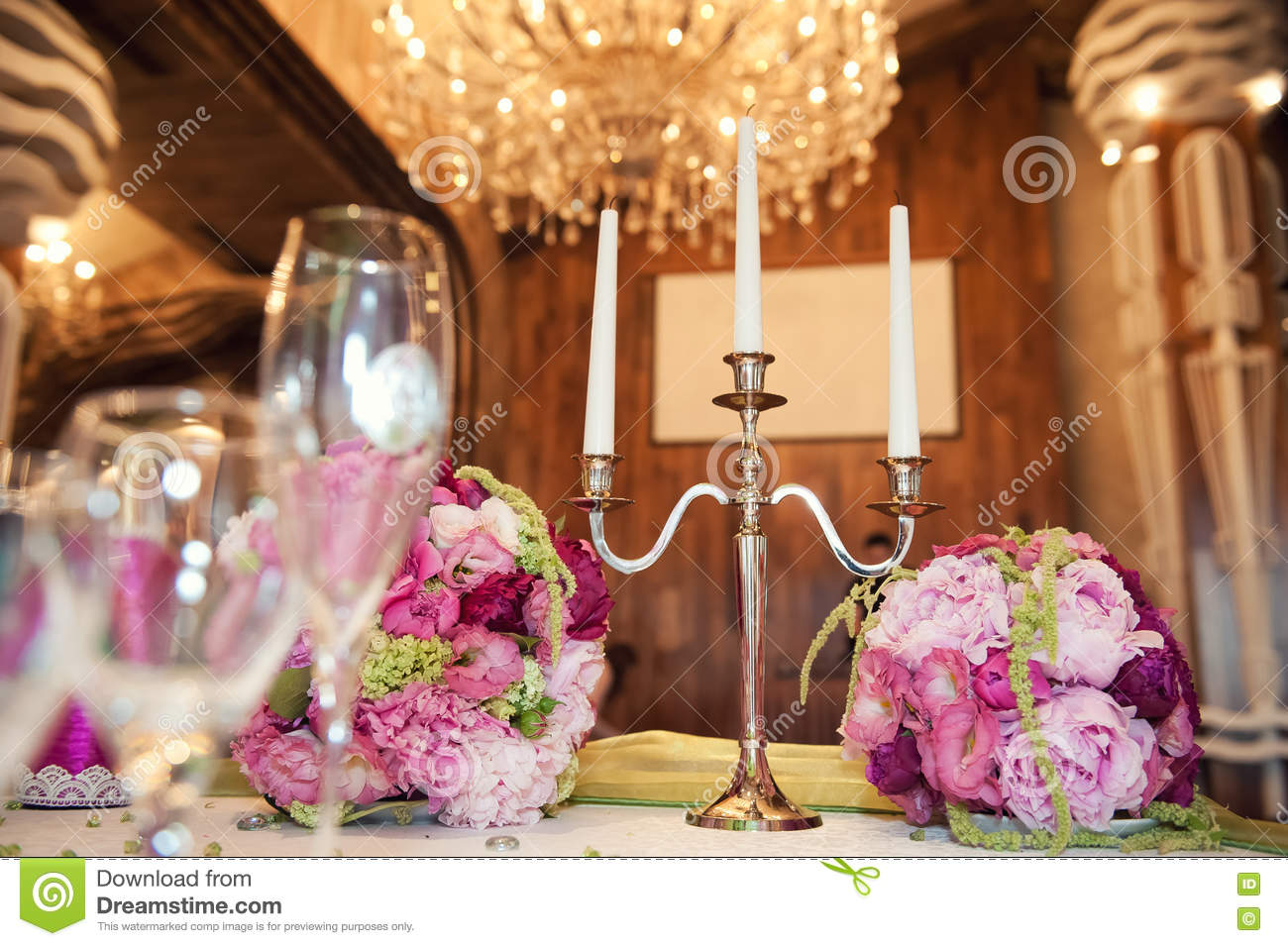 Gorgeous Flower Arrangement At The Wedding Table And Candleholder For Three Candles On Background Of Elegant Chandeliers