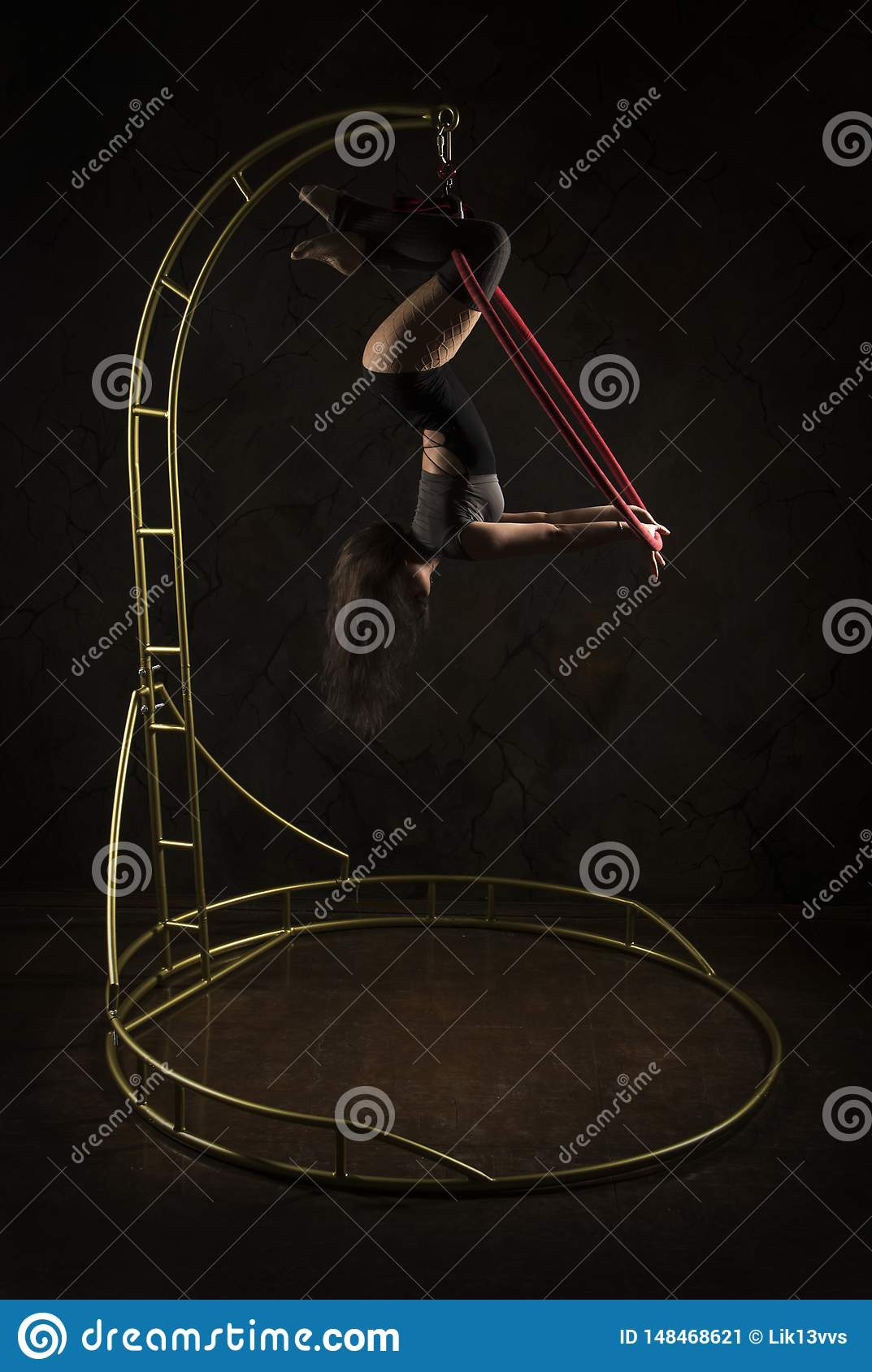 Gorgeous girl, aerial acrobat, in a dark suit performs acrobatic elements on a portable air ring, in the stage light