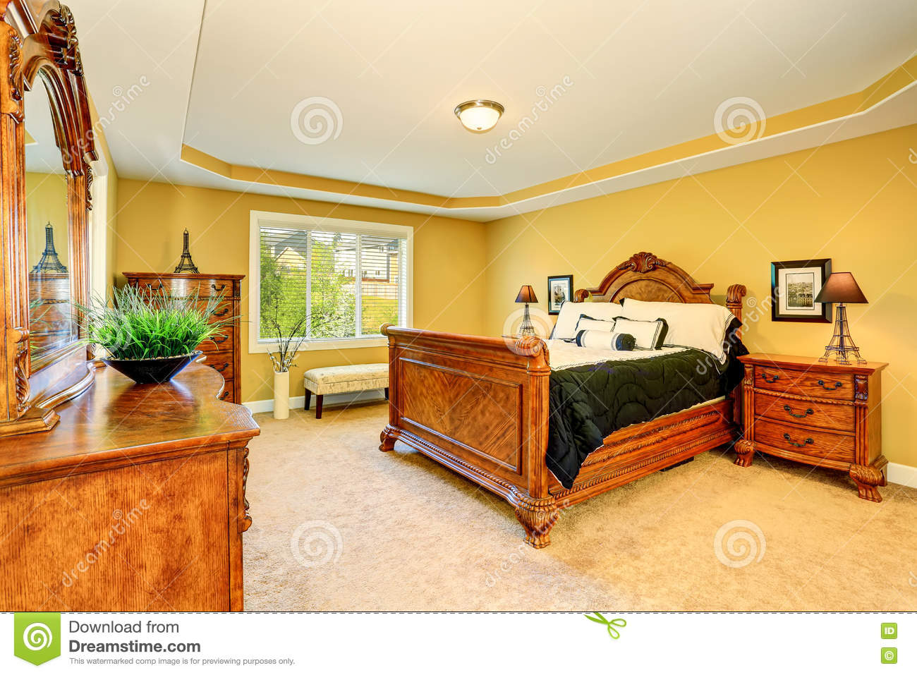 Gorgeous Interior of master bedroom with carved wood bed, nightstand, vanity cabinet with mirror, chest of drawers and carpet floor. Northwest, USA