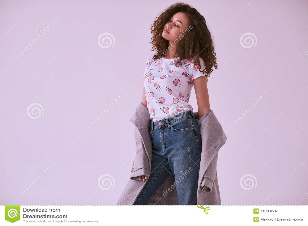 e13cf9b0e0c Gorgeous portrait of elegant black hipster woman with curly hair in coat  and jeans on white background