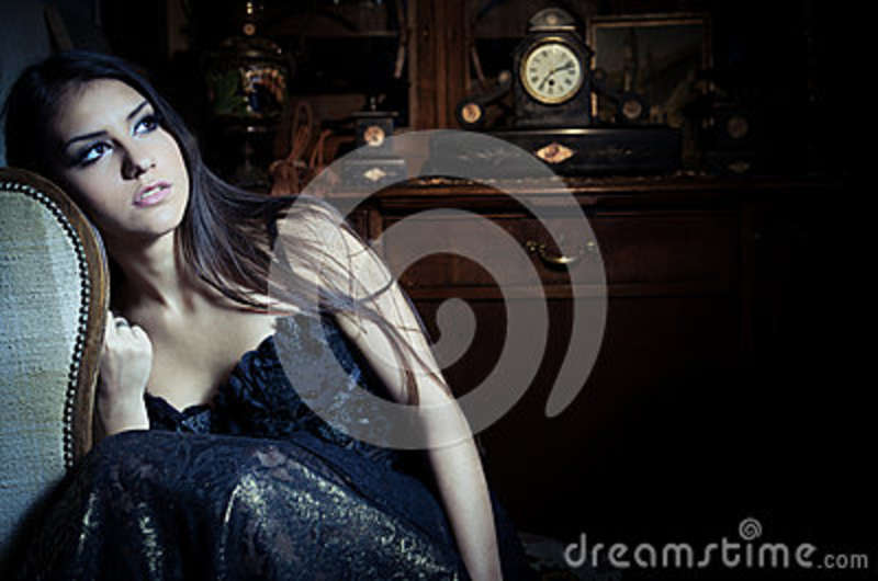 Gorgeous brunette woman in vintage interior with vintage closet and old clock in background and makeup sitting in a chair