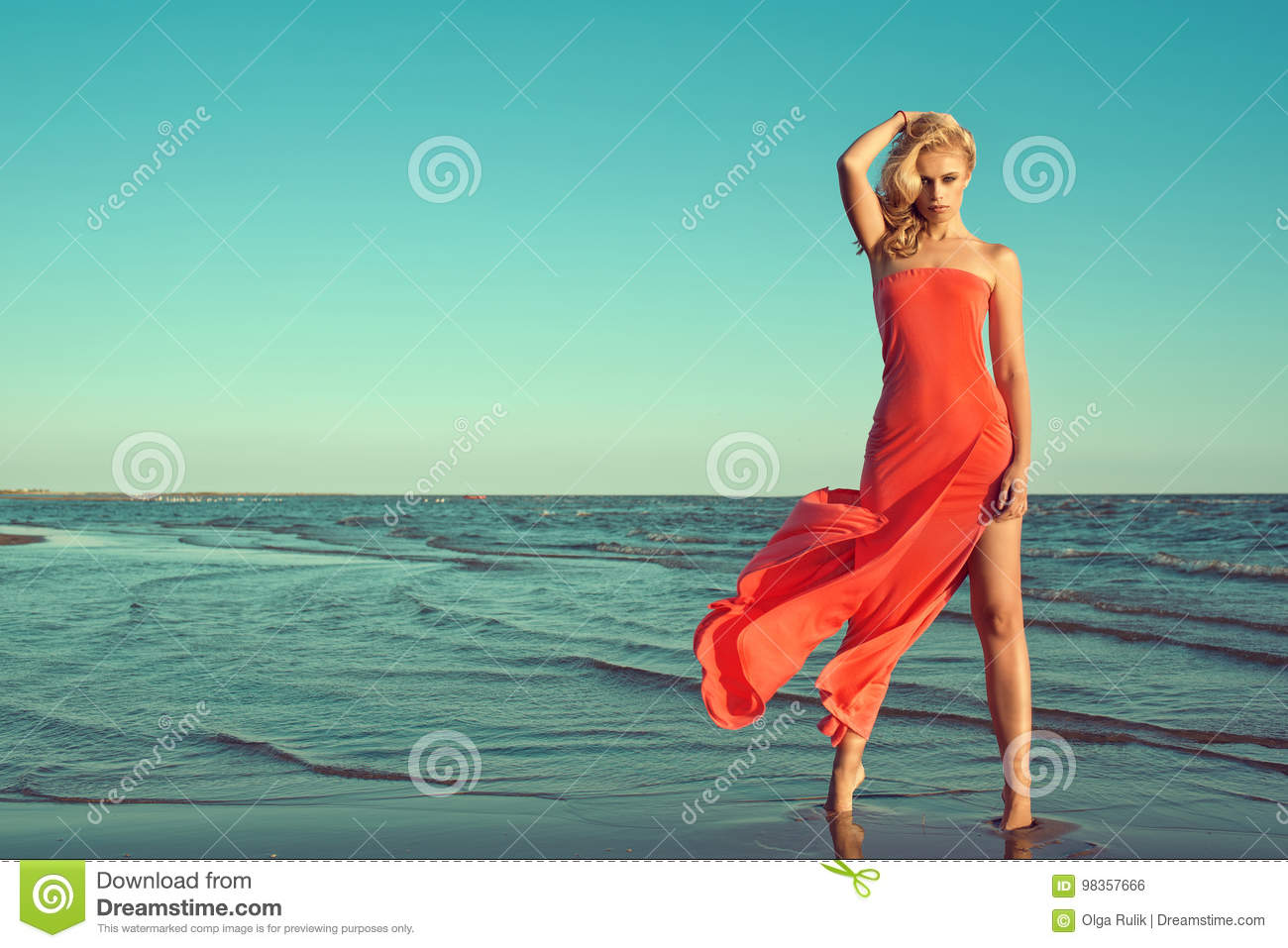 Gorgeous slim blond model in red strapless dress with flying train standing on tiptoe in the sea water