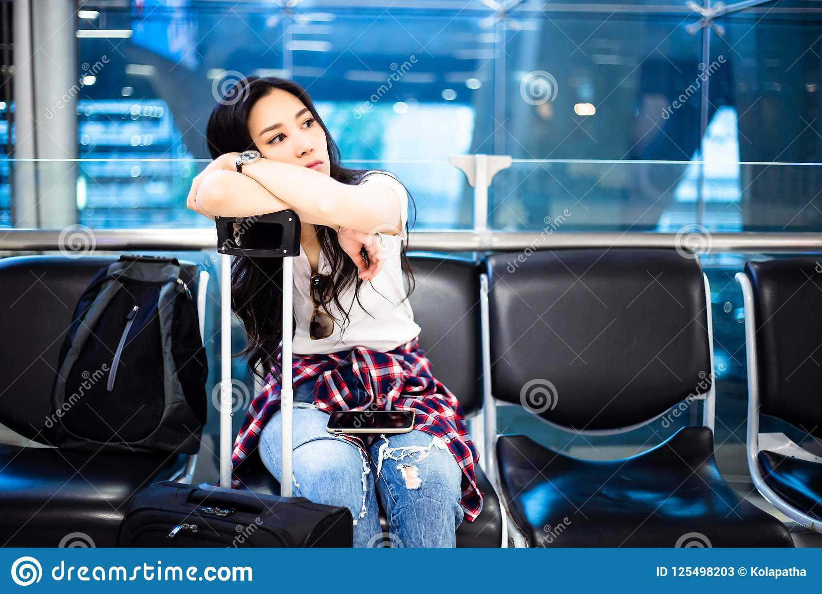 Gorgeous traveler girl sit on a chair at airport. Beautiful woman is waiting airline calling. The airline postpone for takeoff. I