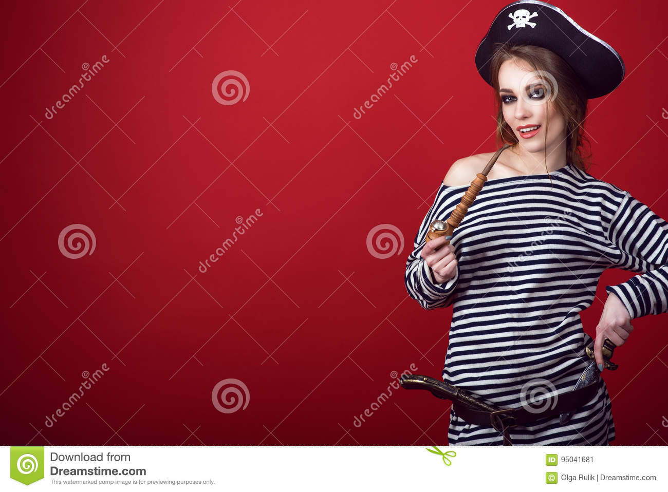 Gorgeous woman with provocative make-up wearing pirate costume and cocked hat holding a wooden carved tobacco pipe