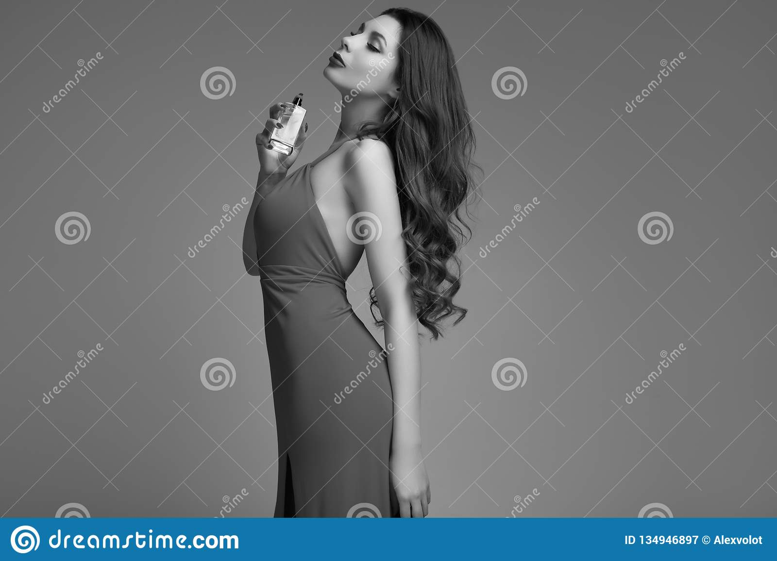 da5f205b98 Portrait of gorgeous young brunette woman with curly hair in red dress  posing at studio background