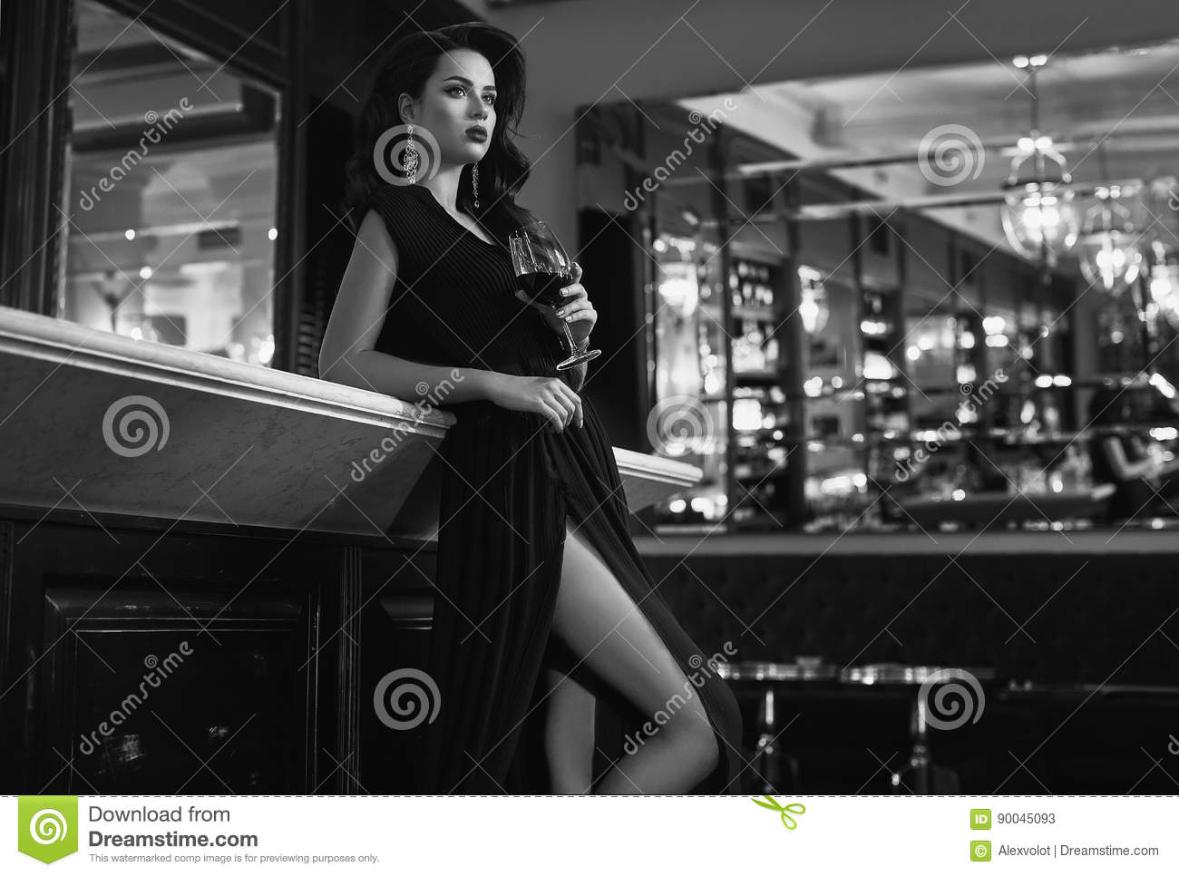 Gorgeous young brunette woman in dark dress with wine