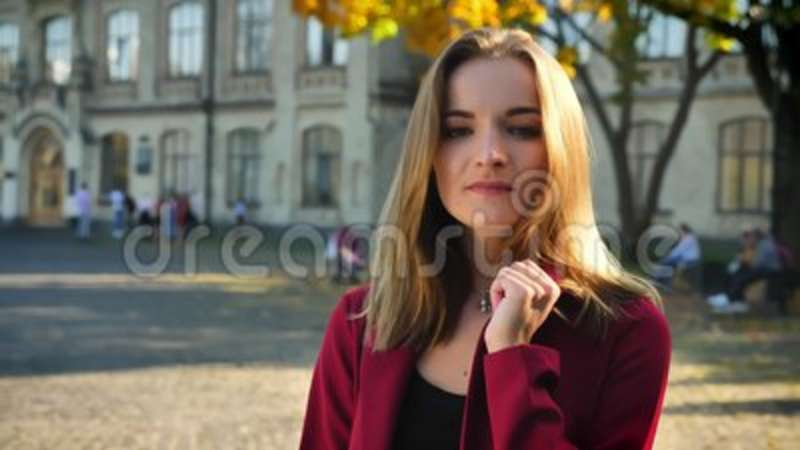 Gorgeous young female student playing with her hair and fixing her suit, looking on a camera, standing on the background. Of university stock video