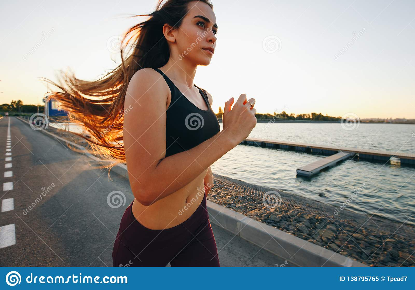 Gorgeous young girl with long brown hair in a sports top and tights runs on the road along the reservoir on the sunset